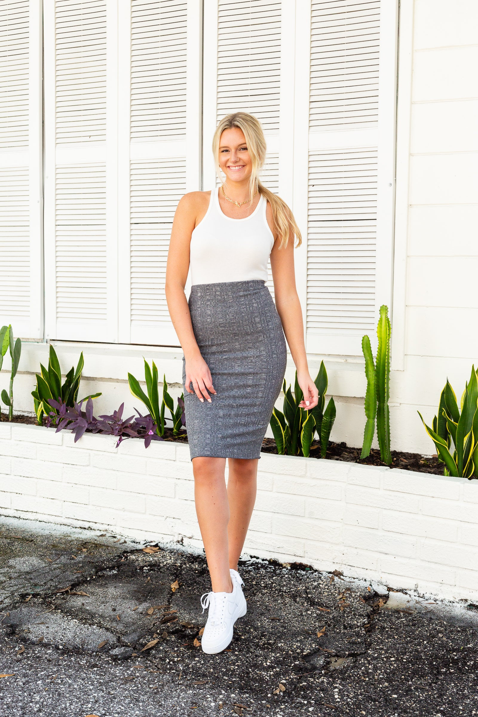 Elastic waistband on a fitted and hip-hugging pencil skirt silhouette with gentle lettuce ruffled hem on the bottom.