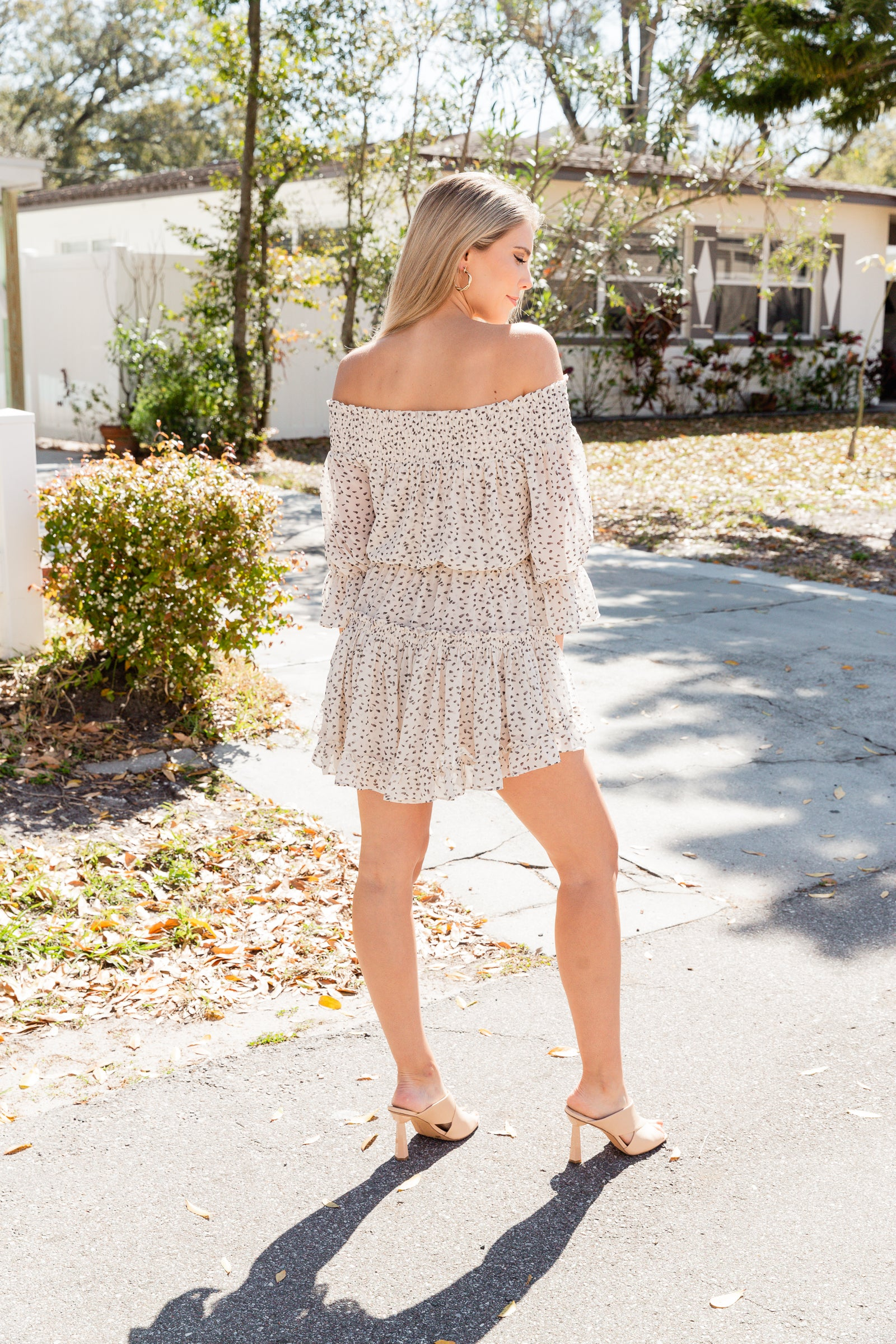 Mid-length ruffle cuffed sleeves attach to an off-the-shoulder and straight neckline that is smocked with a relaxed bodice meets an elastic waistband before going into a tiered ruffle mini skirt.