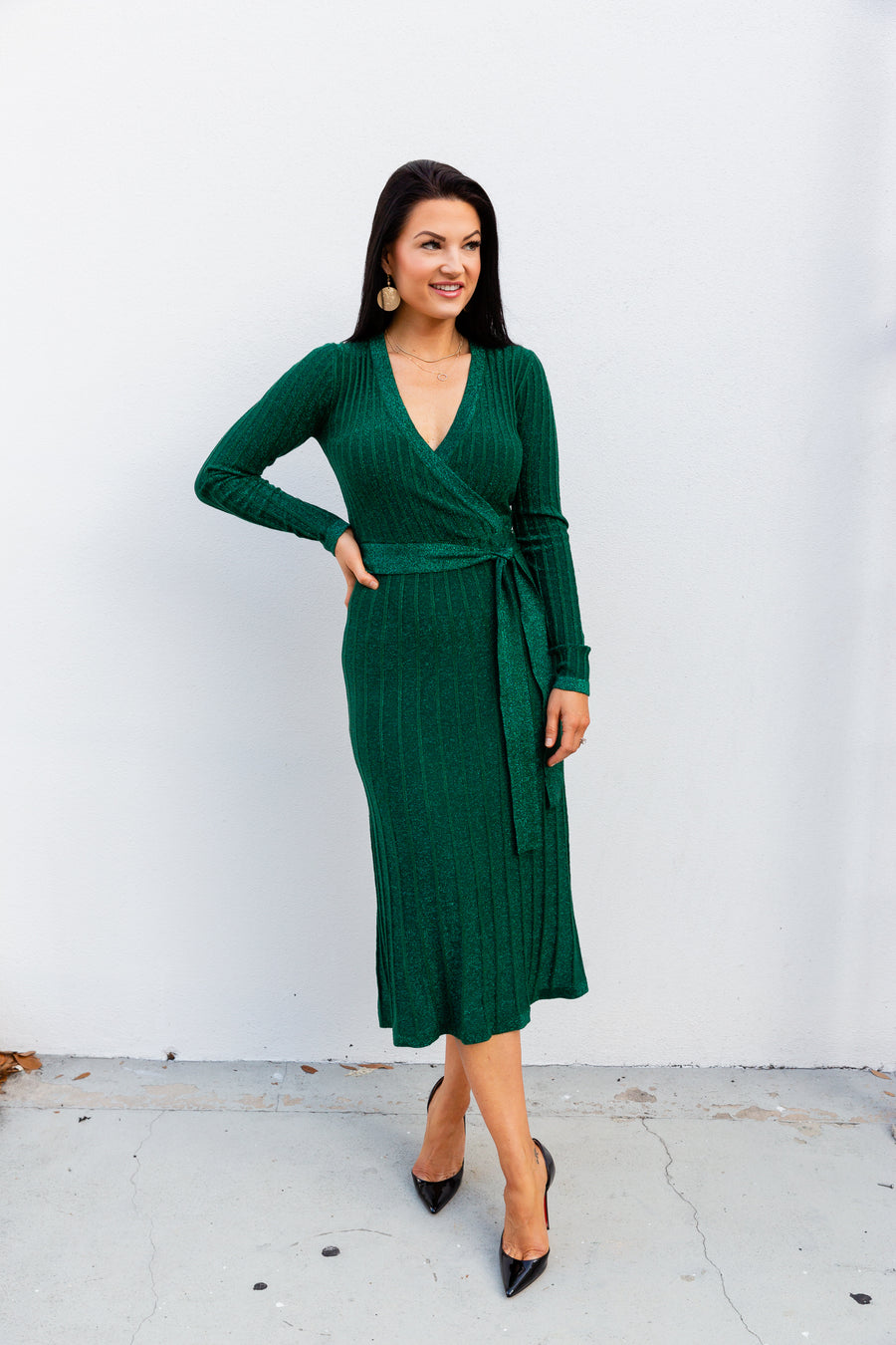 Long fitted sleeves that attach to a deep surplice neckline on a ribbed and fitted bodice before meeting a fitted waist and flowing down into a long and bias-cut midi skirt.