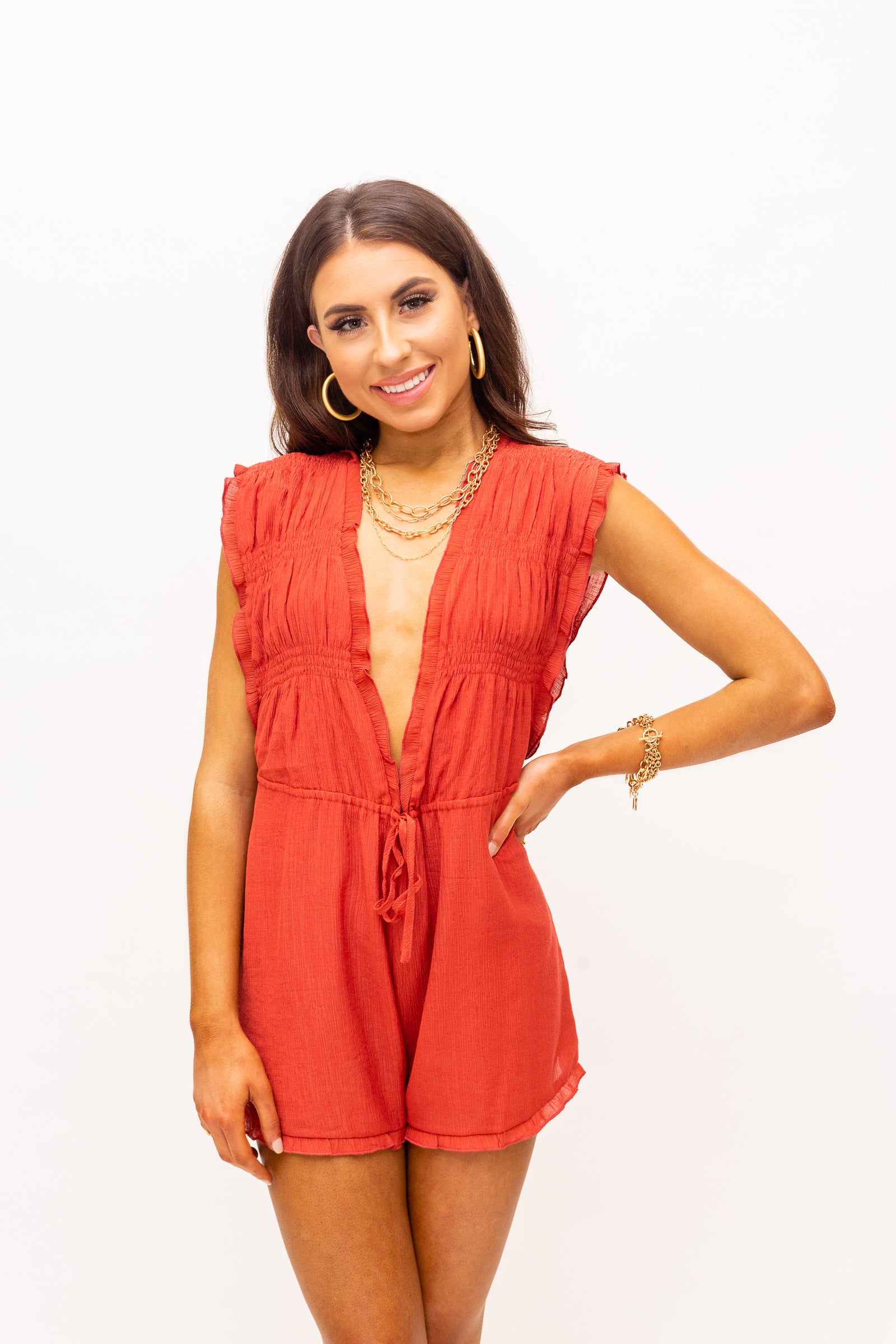 Thick ruffle straps attach to a plunging v-neckline with an oversized smocked bodice before meeting a drawstring waist and flow into comfortable and relaxed shorts with a ruffle hem at the bottom.