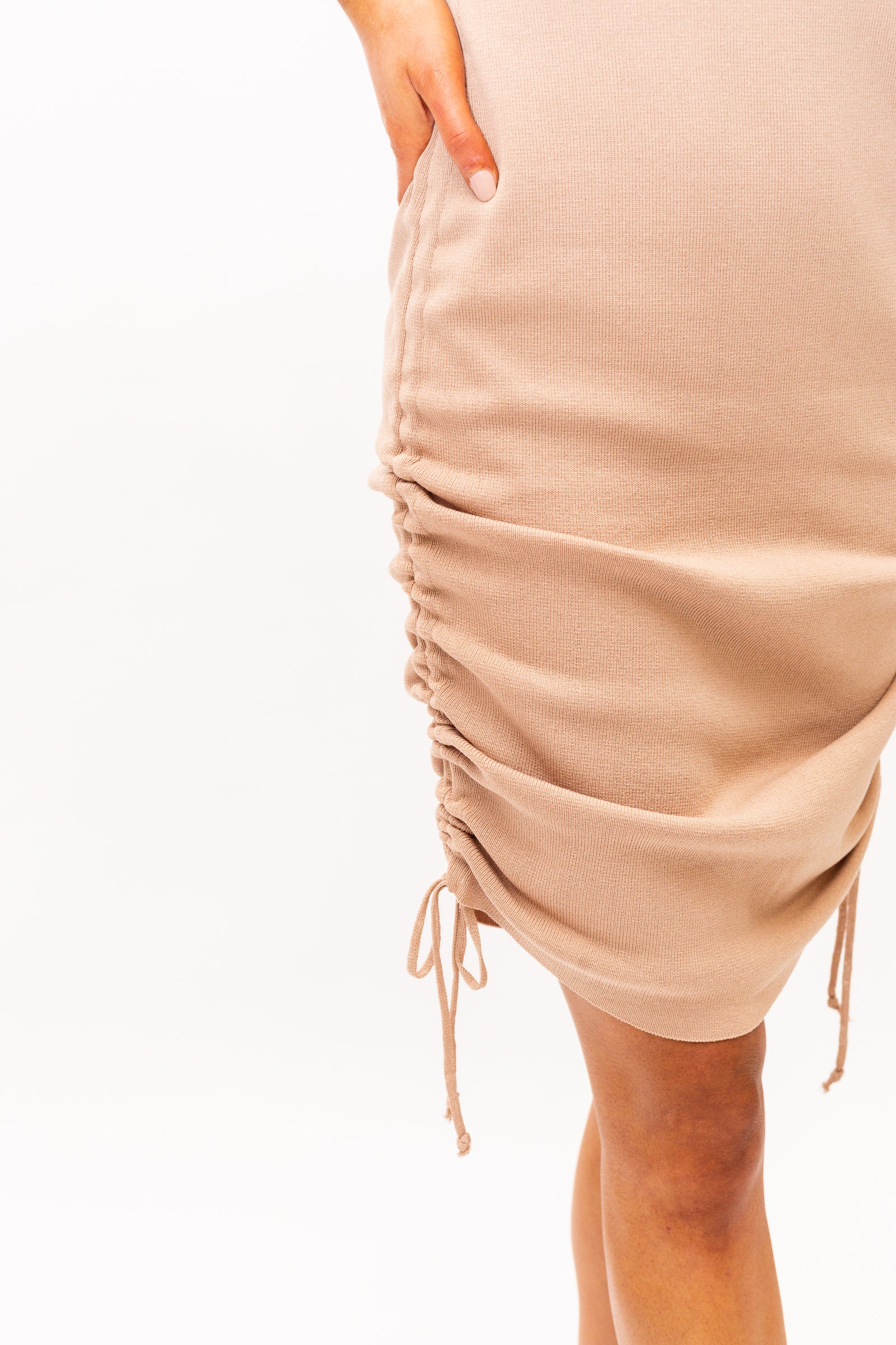 Medium straps attach to a u-neckline on a fitted ribbed bodycon bodice that goes down into a midi skirt with drawstrings on the sides to customize the ruching details on the skirt.