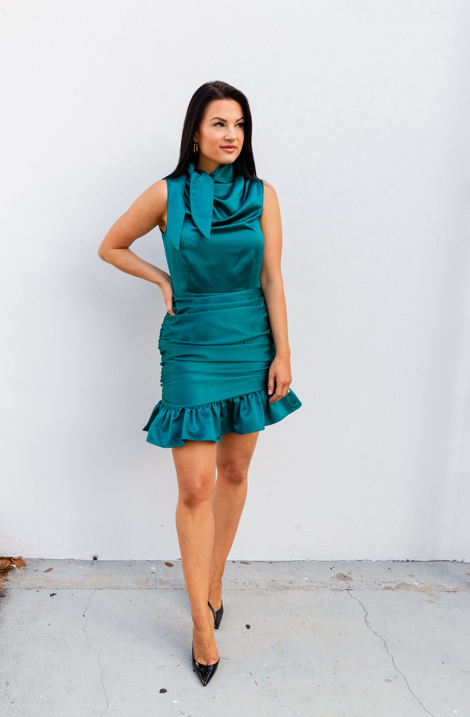 High mock neckline with a tie hem leading to a ruched and darted bodice silhouette meets a fitted waistband before going down into a ruched and gathered mini skirt with a ruffle hem at the bottom.
