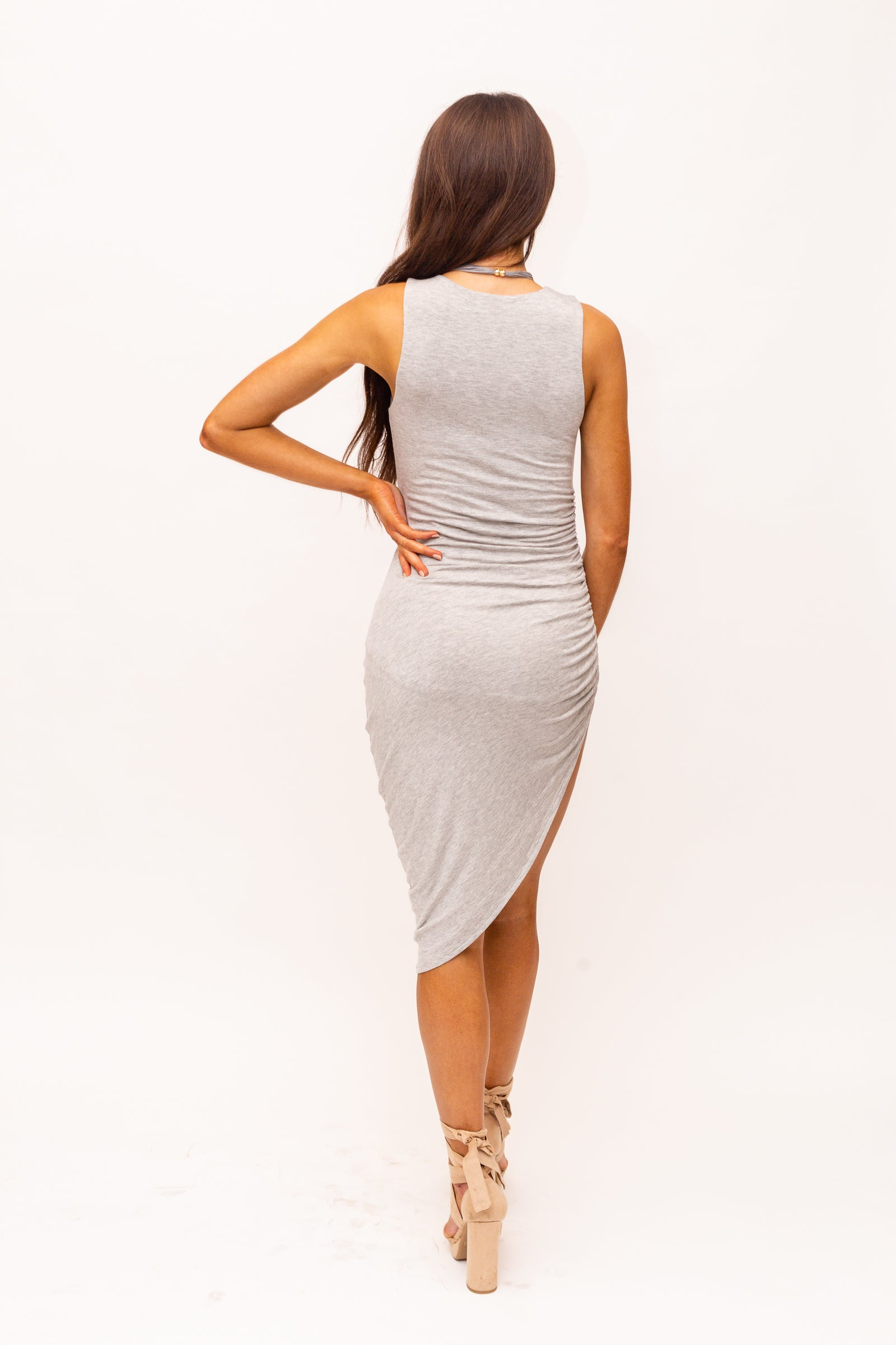 Medium straps attach to a high u-neckline on a fitted bodycon bodice and flow down into an asymmetrical fitted midi skirt with a ruched hem at one side creating a sexy high slit detail as it gathers.