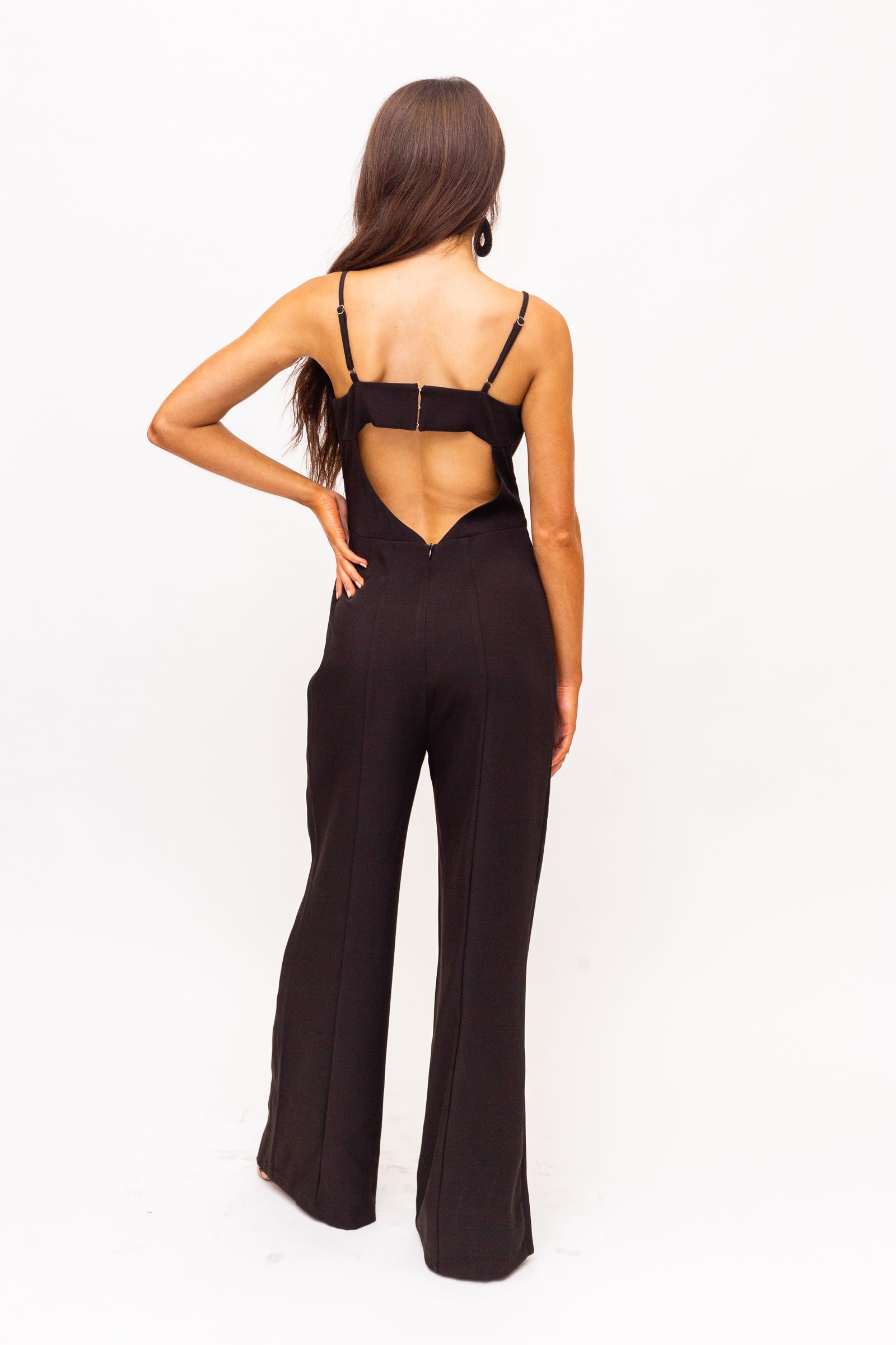 Thin adjustable straps attach to a deep v-notched neckline with a scalloped breast paneling on a fitted and darted bodice before flowing down into long and straight pant legs.