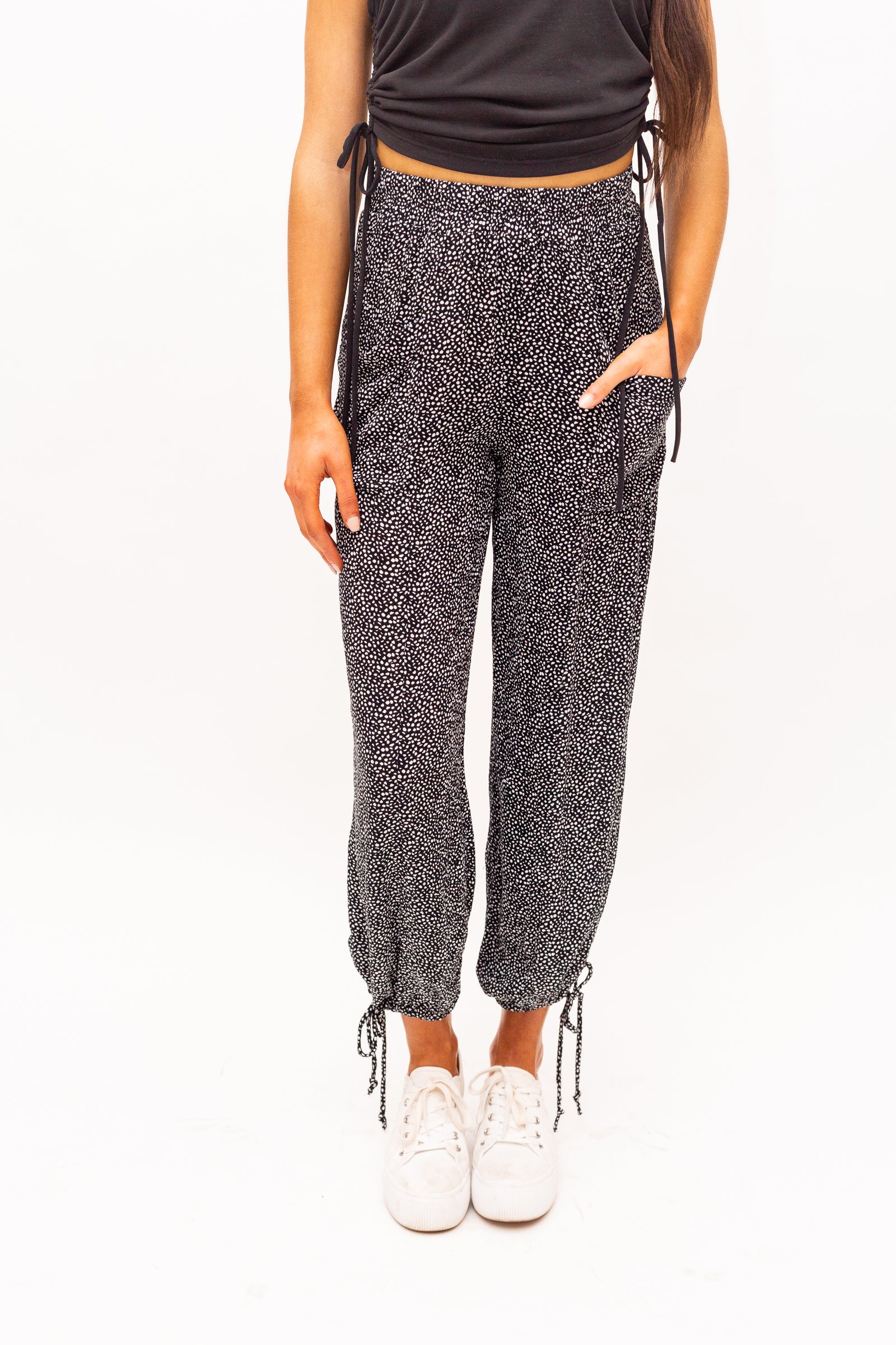 Dotted pants have an elastic waistband and lead to a loose and relaxed fit balloon pants with front pockets and taper into comfortable pant legs with drawstring tied cuffs at the ankles.