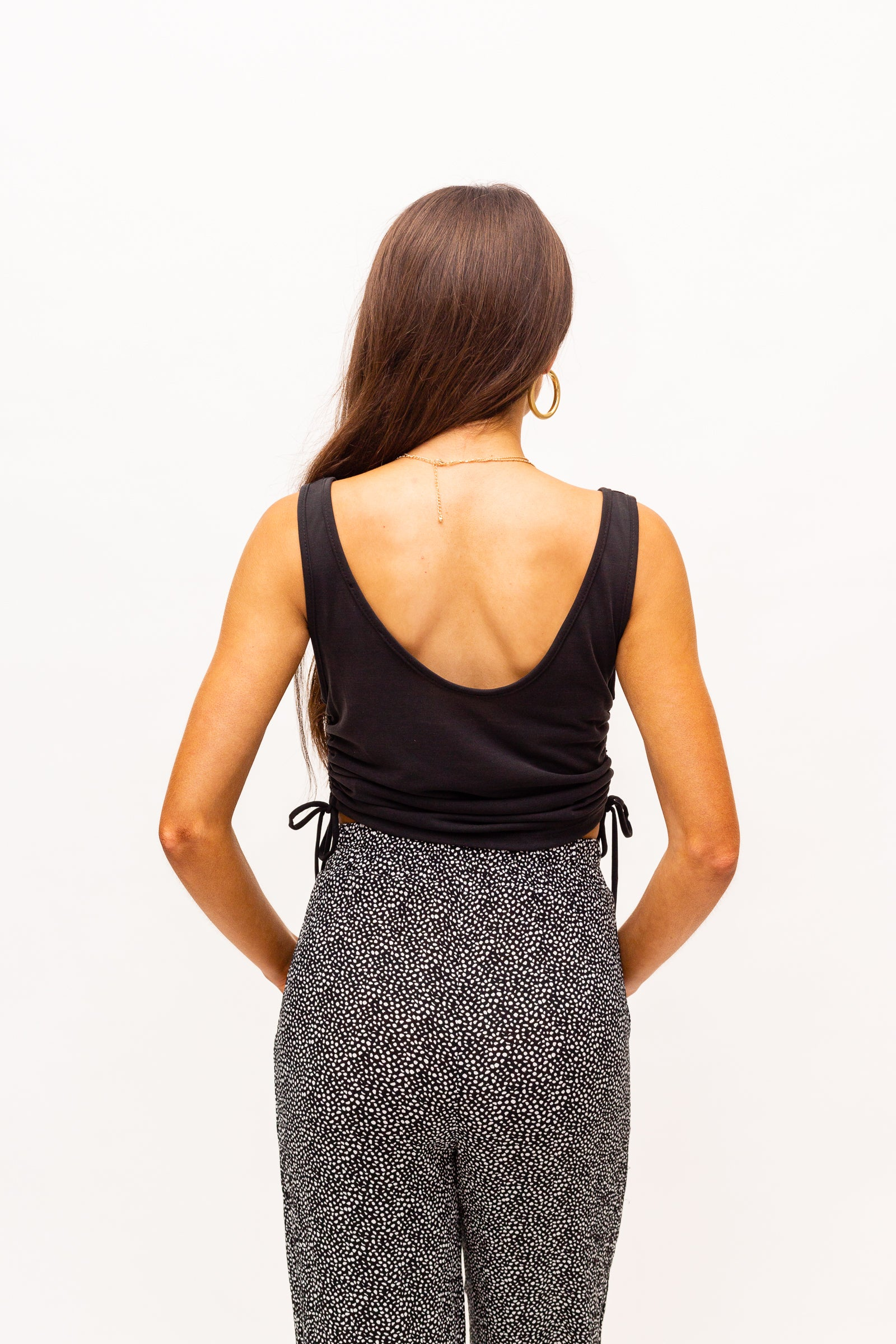 Medium straps attach to a u-neckline on a loose-fit and relaxed cropped bodice with drawstrings on the side to customize the ruching effect on the tank top.