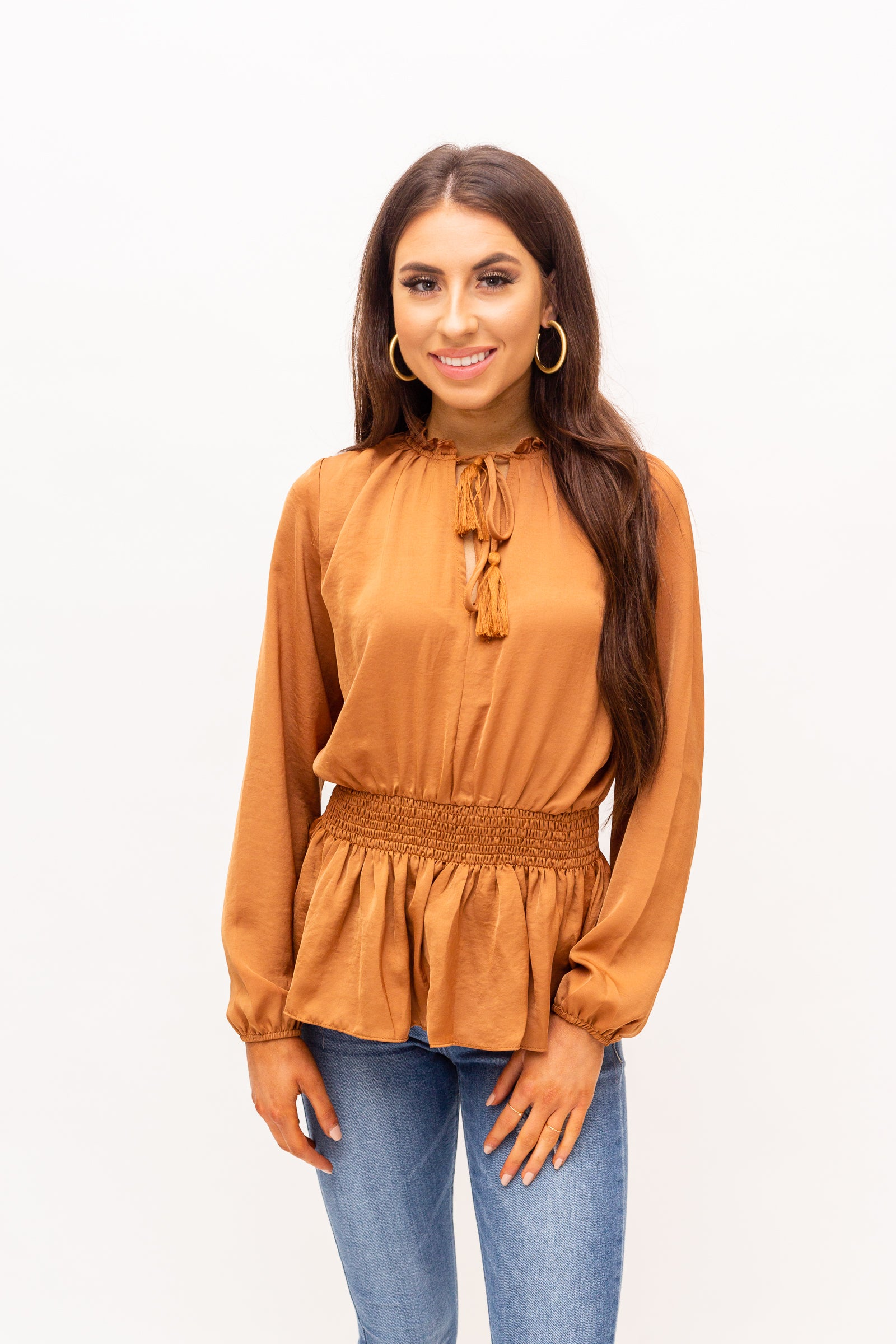 Long elastic cuffed sleeves that attach to a high ruffle v-neckline with a tassel tie that could be secured at the neck on an oversized relaxed bodice with a smocked waist and a peplum style hem.