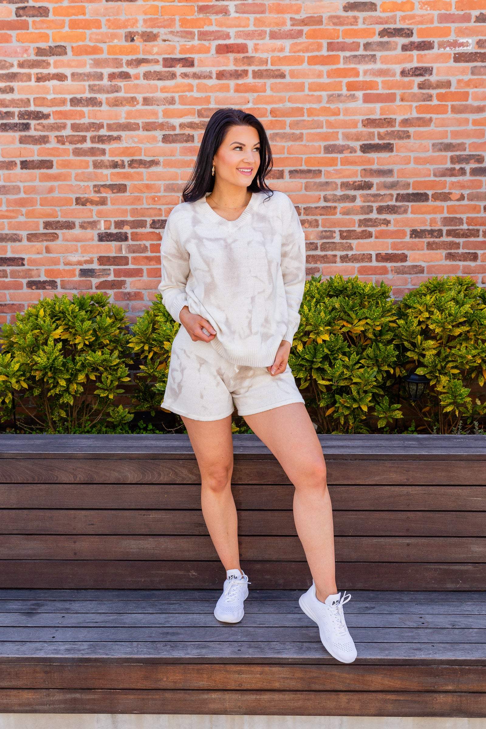 Taupe tie-dye prints cover the fabric of this pullover top. It has long sleeves that attach to a banded v-neckline on an oversized and knit bodice.