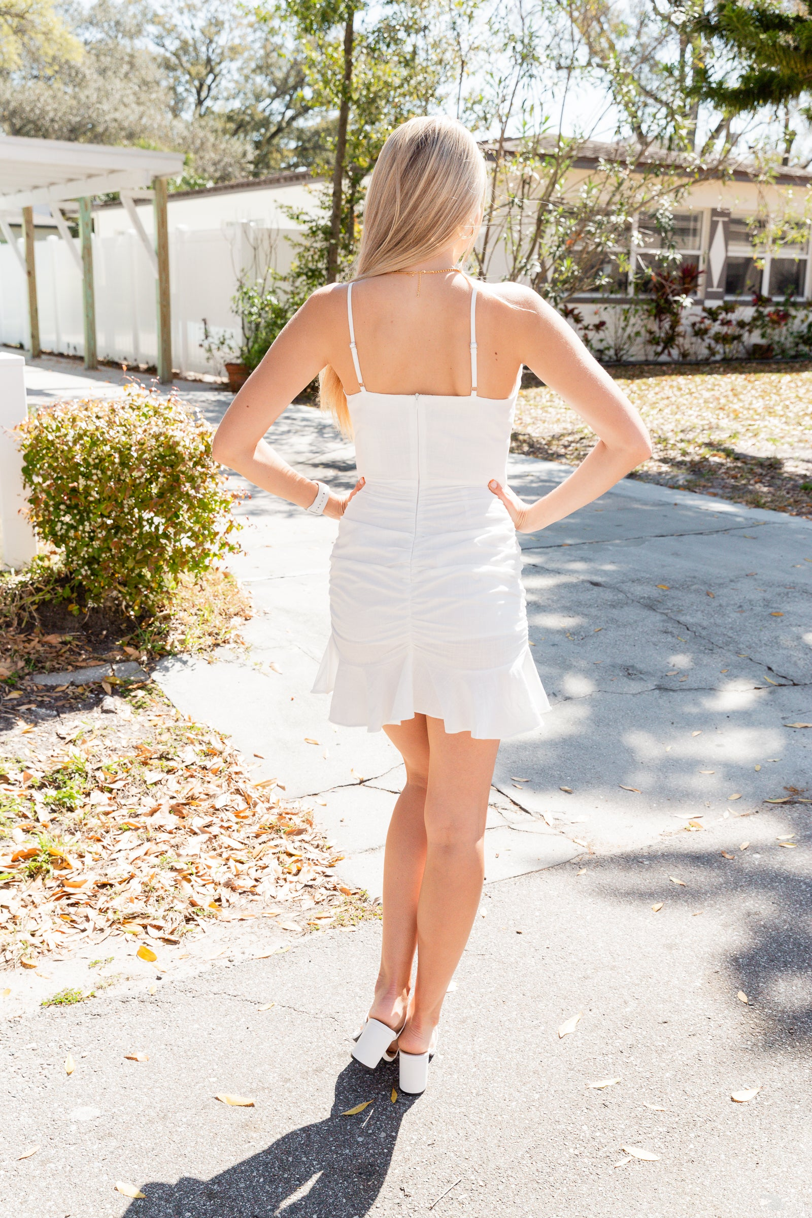 Thin adjustable straps attach to a v-neckline on a boned and fitted bodice that meets a ruched mini skirt with ruffle trim. This white mini dress features a zipper with a hook and eye closure on the back.