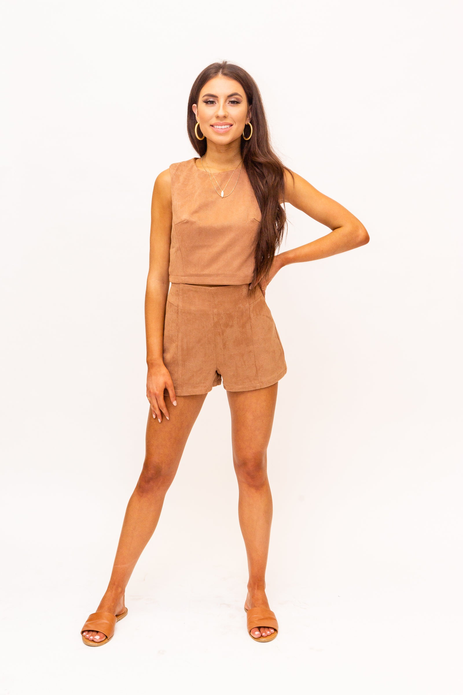Medium straps attach to a high u-neckline on a fitted and darted crop bodice silhouette. This suede top features a zipper down the back of the crop top.