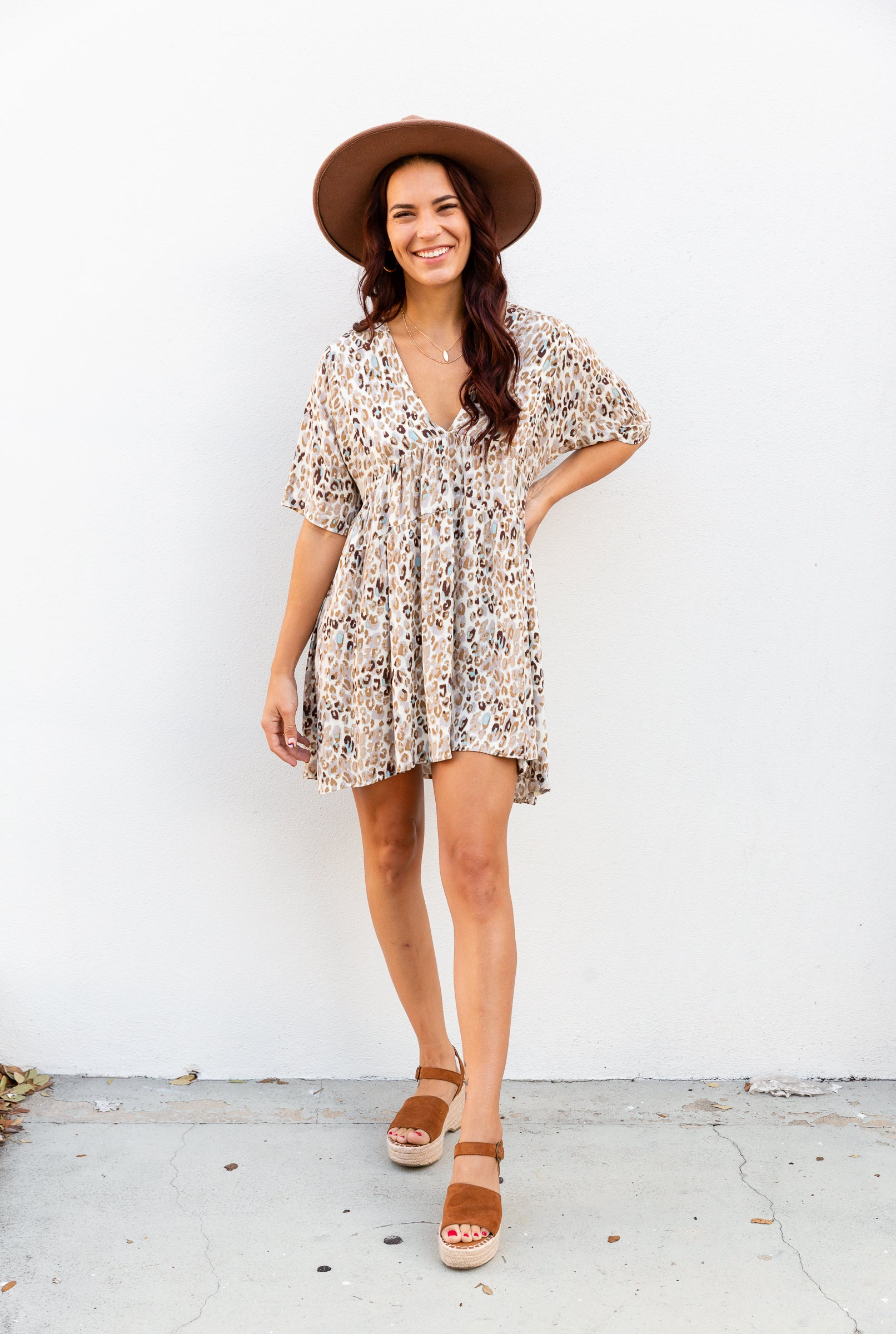 Brown and taupe leopard prints cover the fabric. It has short sleeves attach to a v-neckline on an oversized and relaxed-fit bodice before flowing down into a baby doll style skirt silhouette.