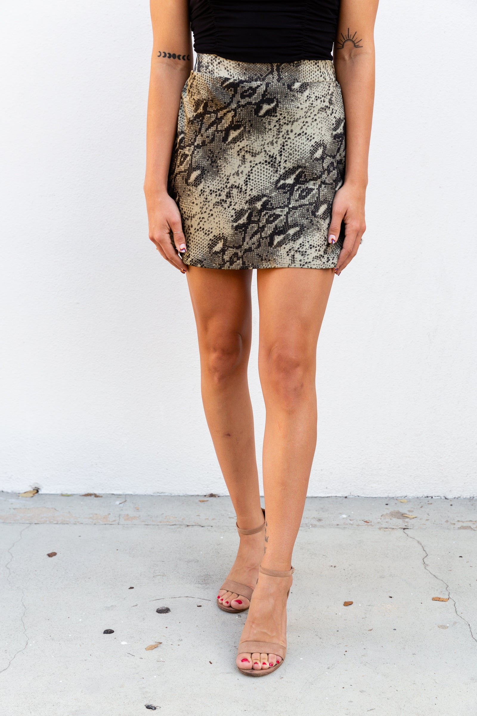 This snake printed skirt is on satiny fabric. It has an elastic waistband that goes down into a flowy bias cut skirt with short bottom hem.