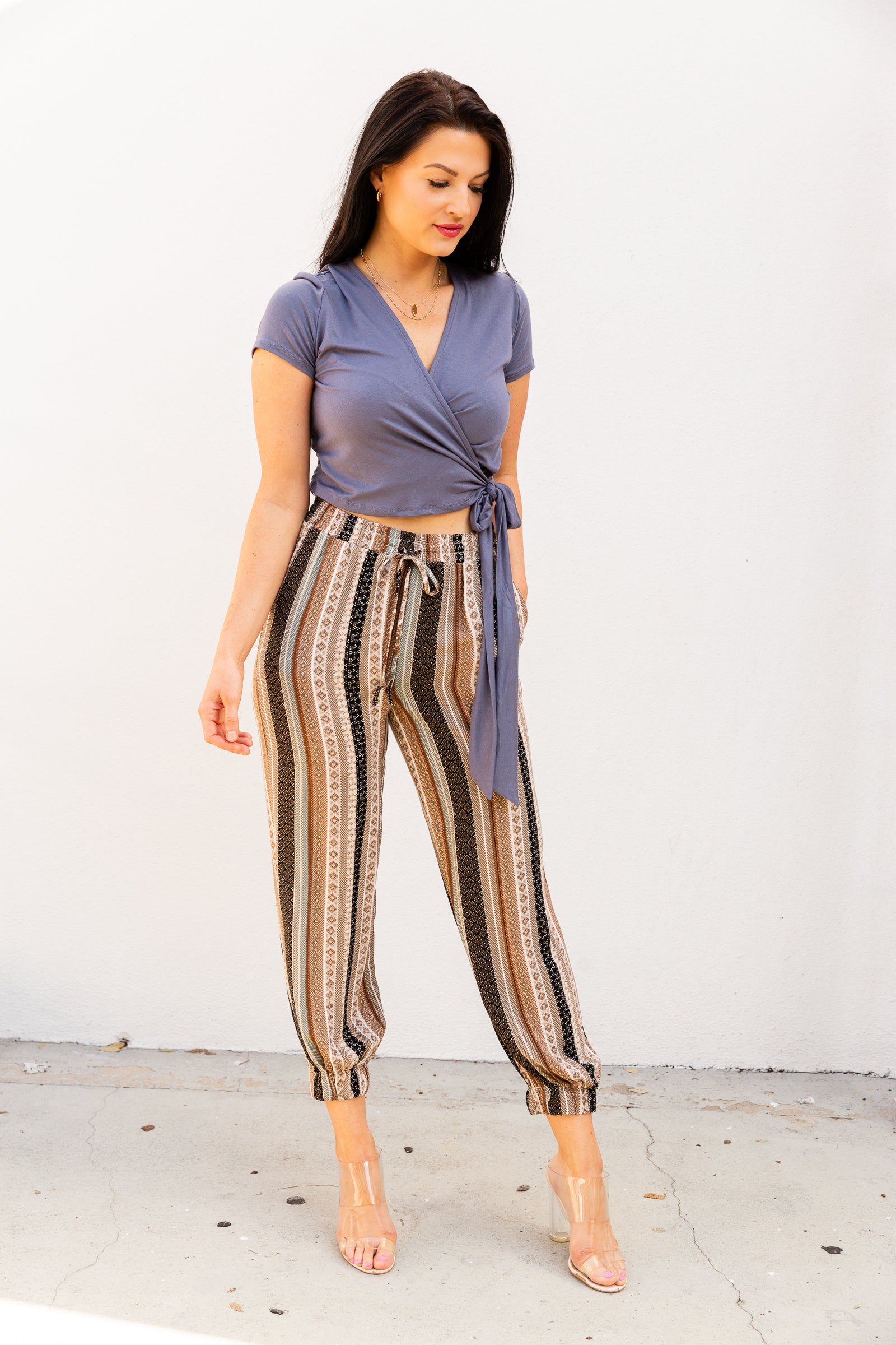 These striped joggers have an elastic waistband with a functional drawstring tie that leads down to relaxed-fitting pants with side pockets and elastic cuffed hems at the ankles.