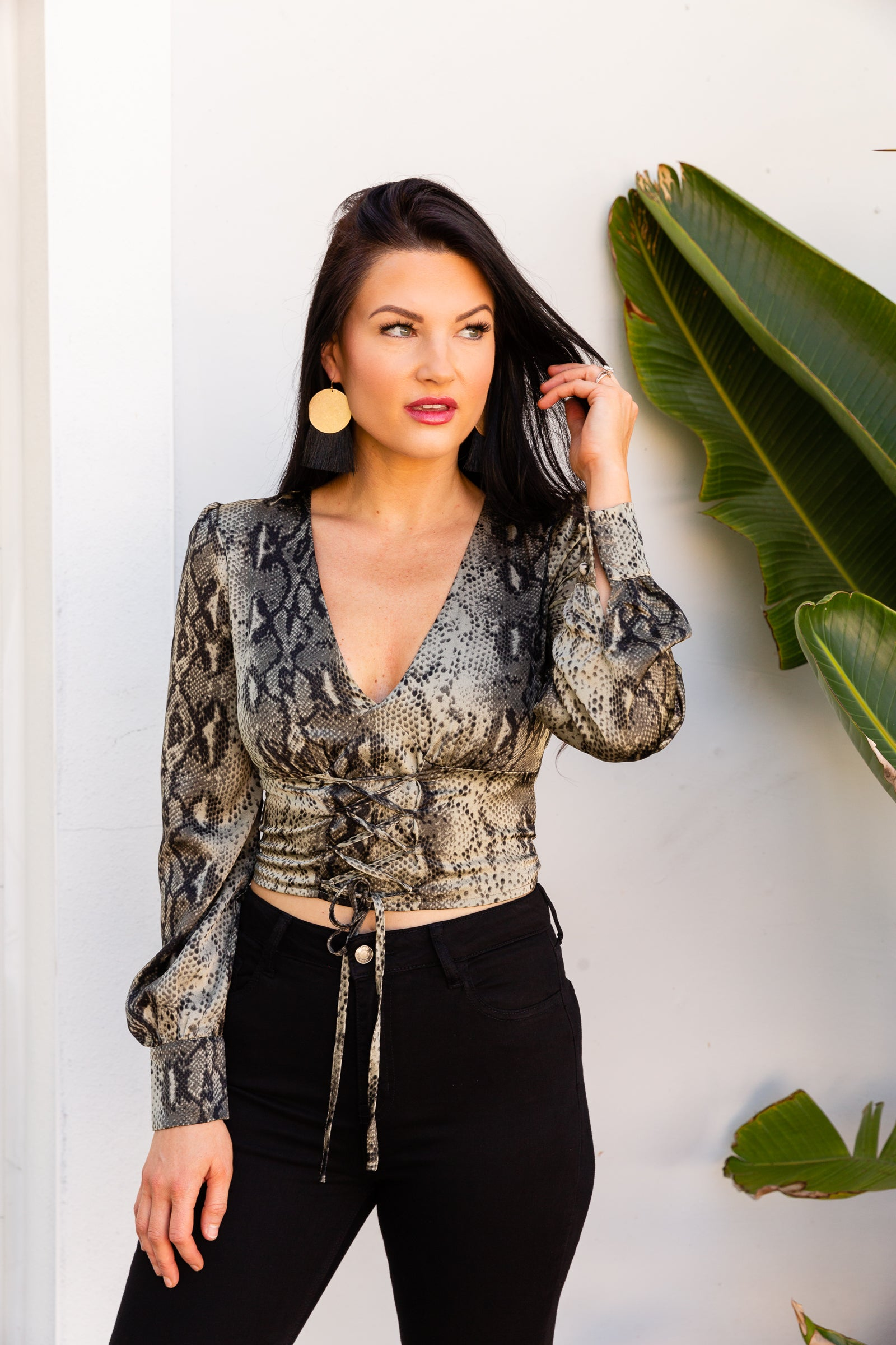 This snake printed top is on satiny fabric, long button cuffed sleeves that attach to a deep v-neckline on a fitted and cropped bodice with crisscrossed tied string detail down the center.