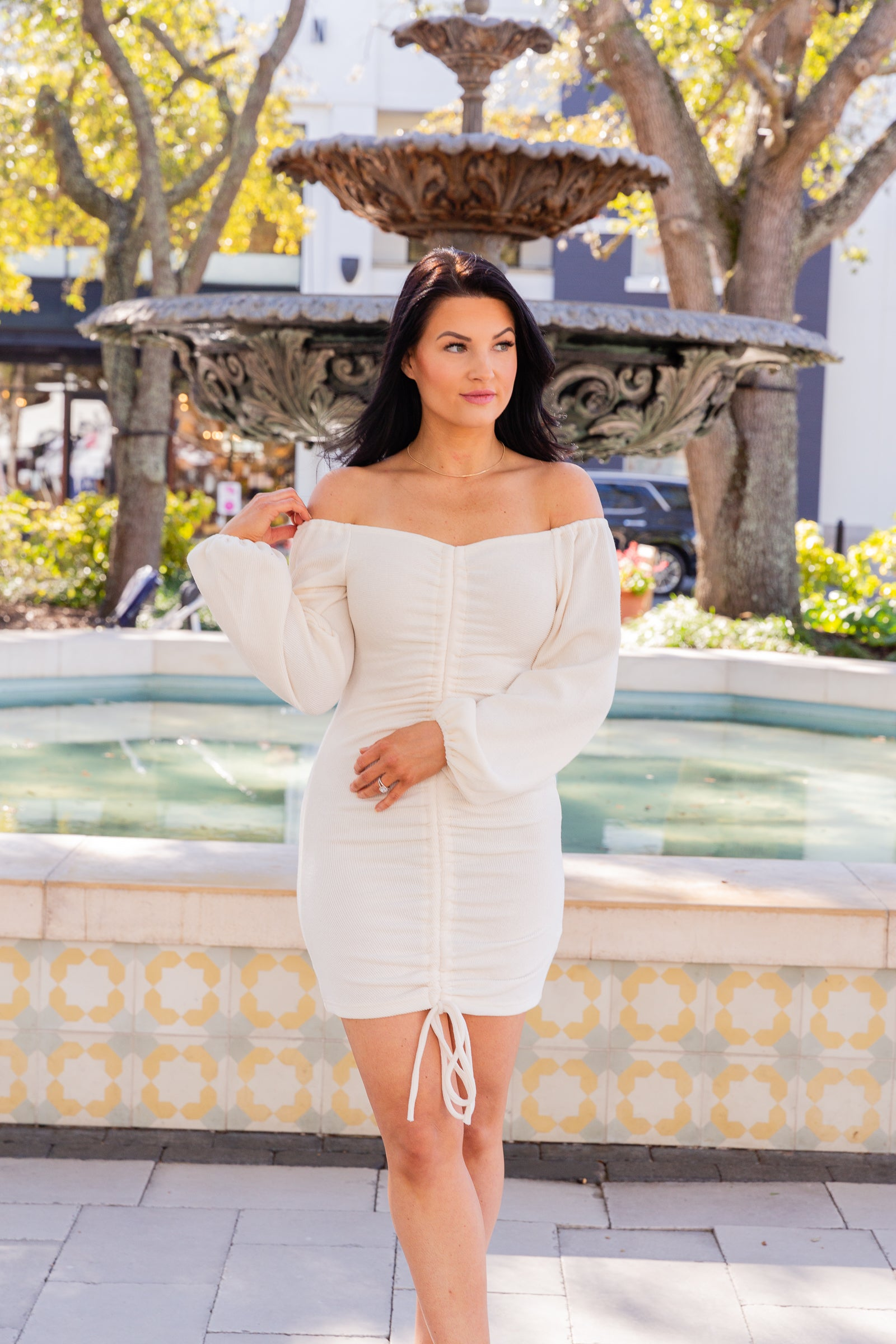 Long elastic cuffed and puffed sleeves attach to an off-the-shoulder sweetheart neckline going into a bodycon bodice silhouette with a drawstring center that ruches the dress and ties at the bottom.