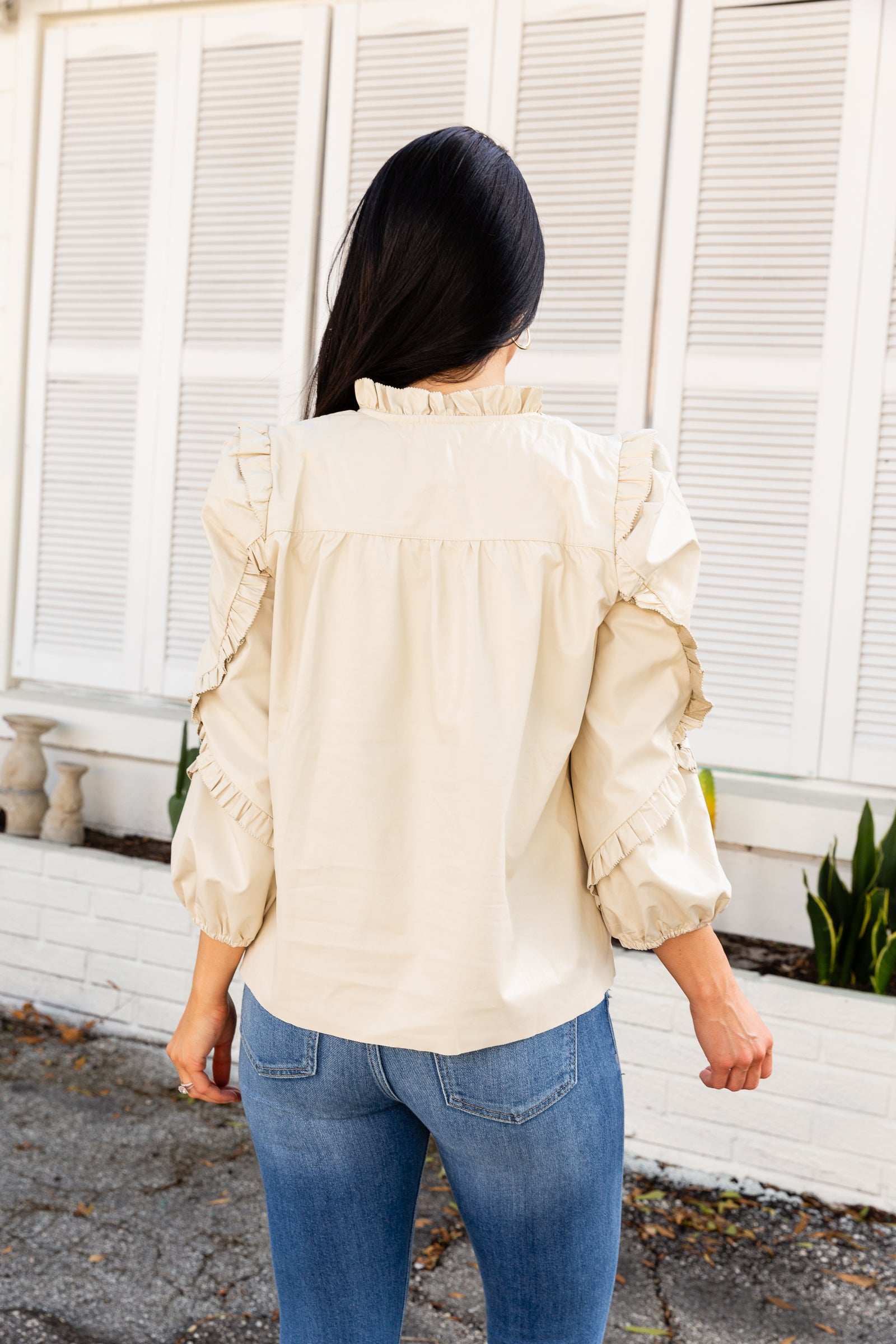 Faux leather blouse has mid-length elastic cuffed and puffed sleeves with ruffled details that attach to a ruffle v-neckline with a tassel tie and an oversized relaxed bodice.