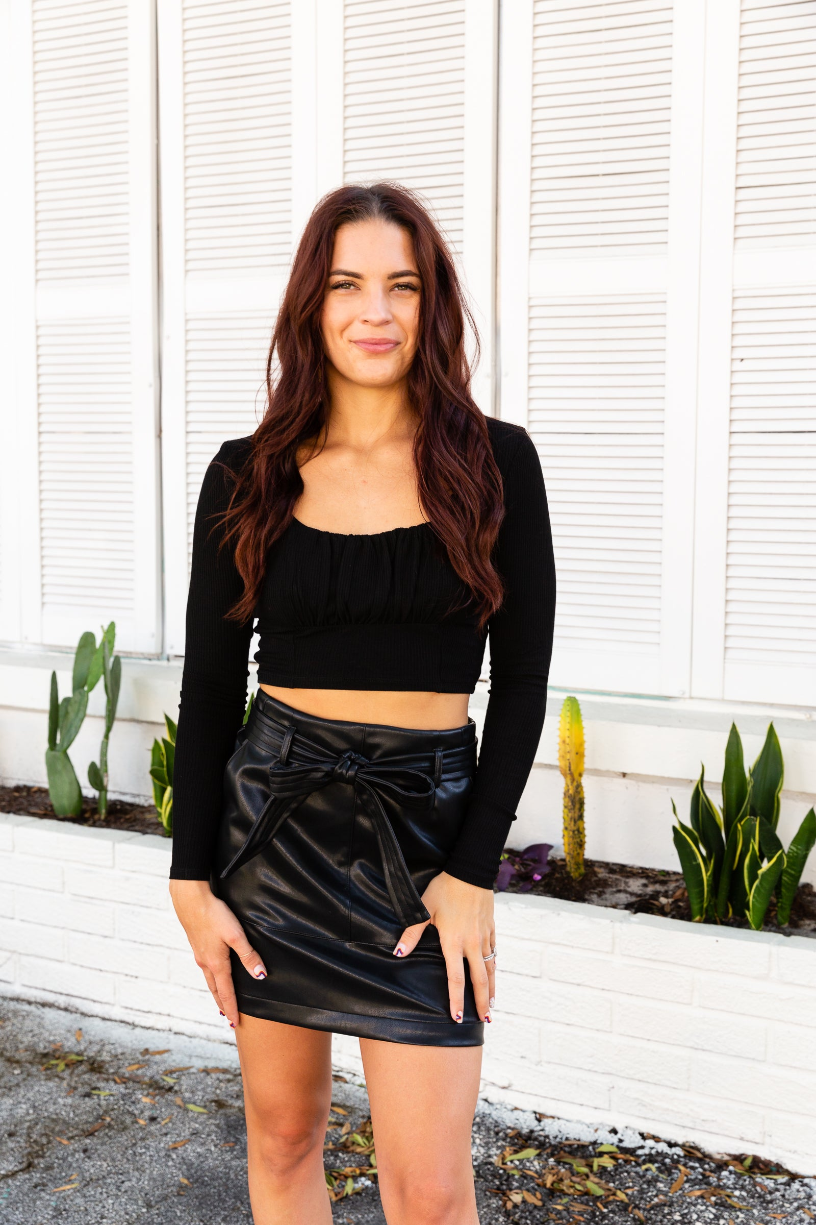 Long fitted sleeves attach to a u-neckline on a knit and fitted bodice with a shirred bust and cropped bottom hem. Style this black crop top with a high-waisted bottoms!
