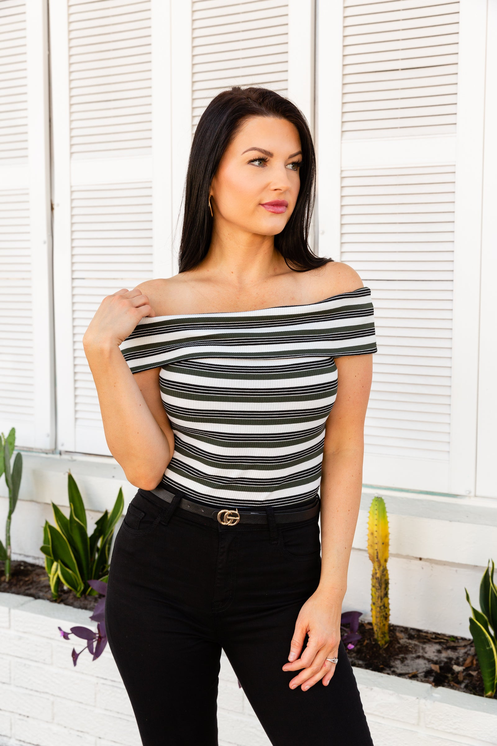Black and olive striped bodysuit has an off-the-shoulder and straight neckline that flows into a fitted bodice and meets cheeky briefs. Features button closures on the inseam.