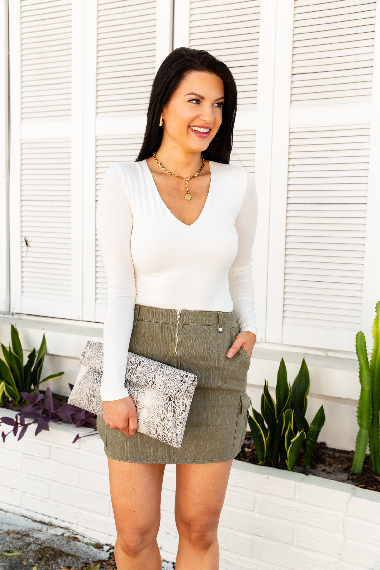 Fitted waistband with belt loops that leads to a zippered center detail on a paneled skirt with a hip-hugging silhouette with side pockets and flapped pockets at each side underneath.