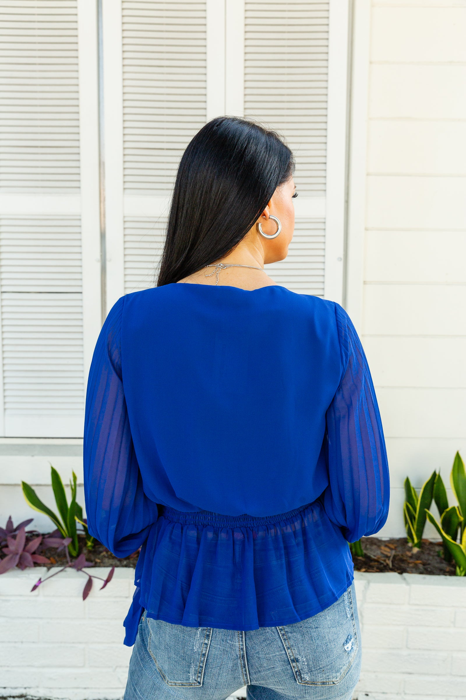 Long pleated button cuffed sleeves that attach to a surplice neckline on a relaxed bodice meeting a fitted waistband with a side tie hem before flowing into a peplum silhouette.