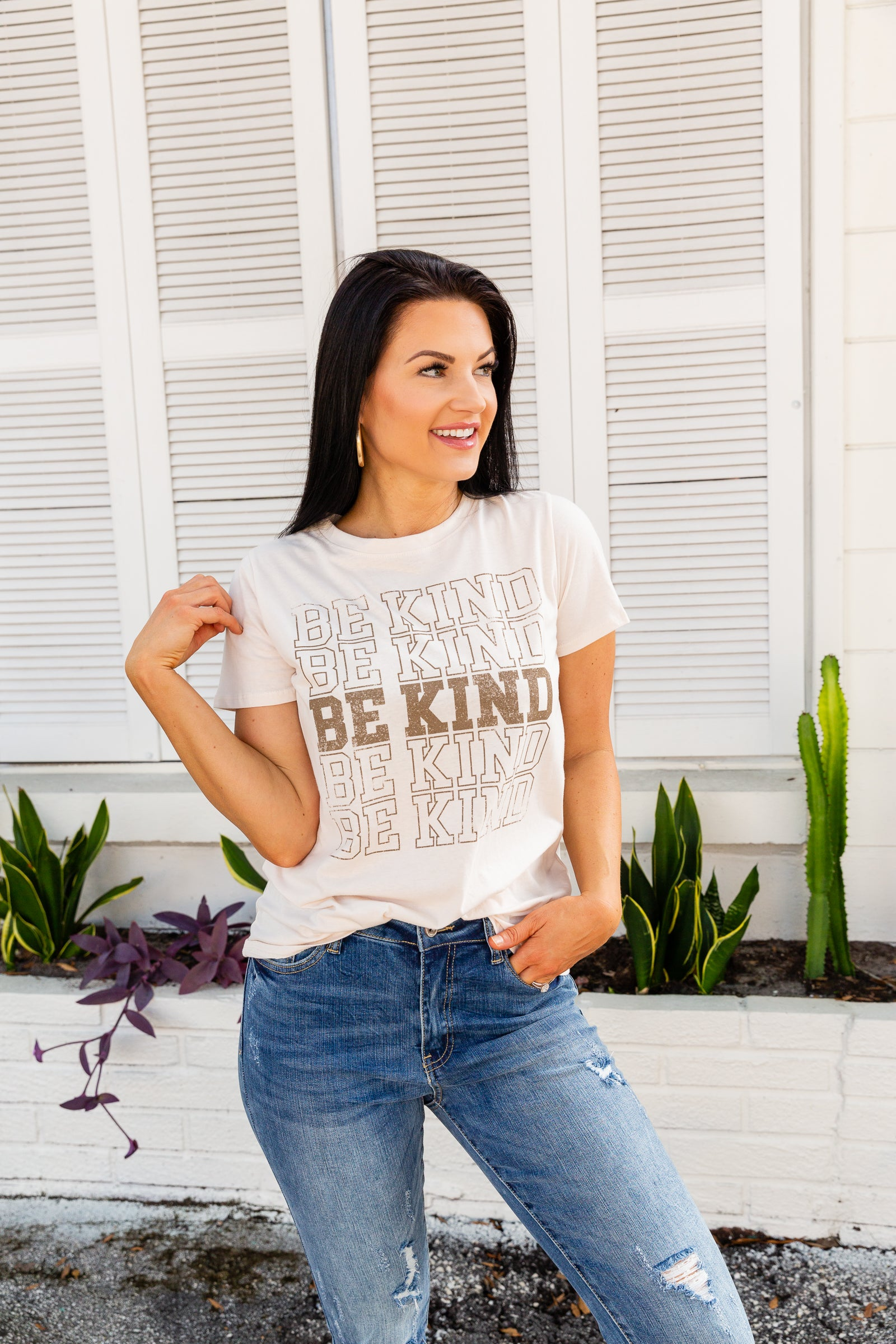 "Short sleeves attach to a u-neckline on a classic relaxed t-shirt style bodice. The words ""Be Kind"" repeat down the center front of the shirt in an outlined font."