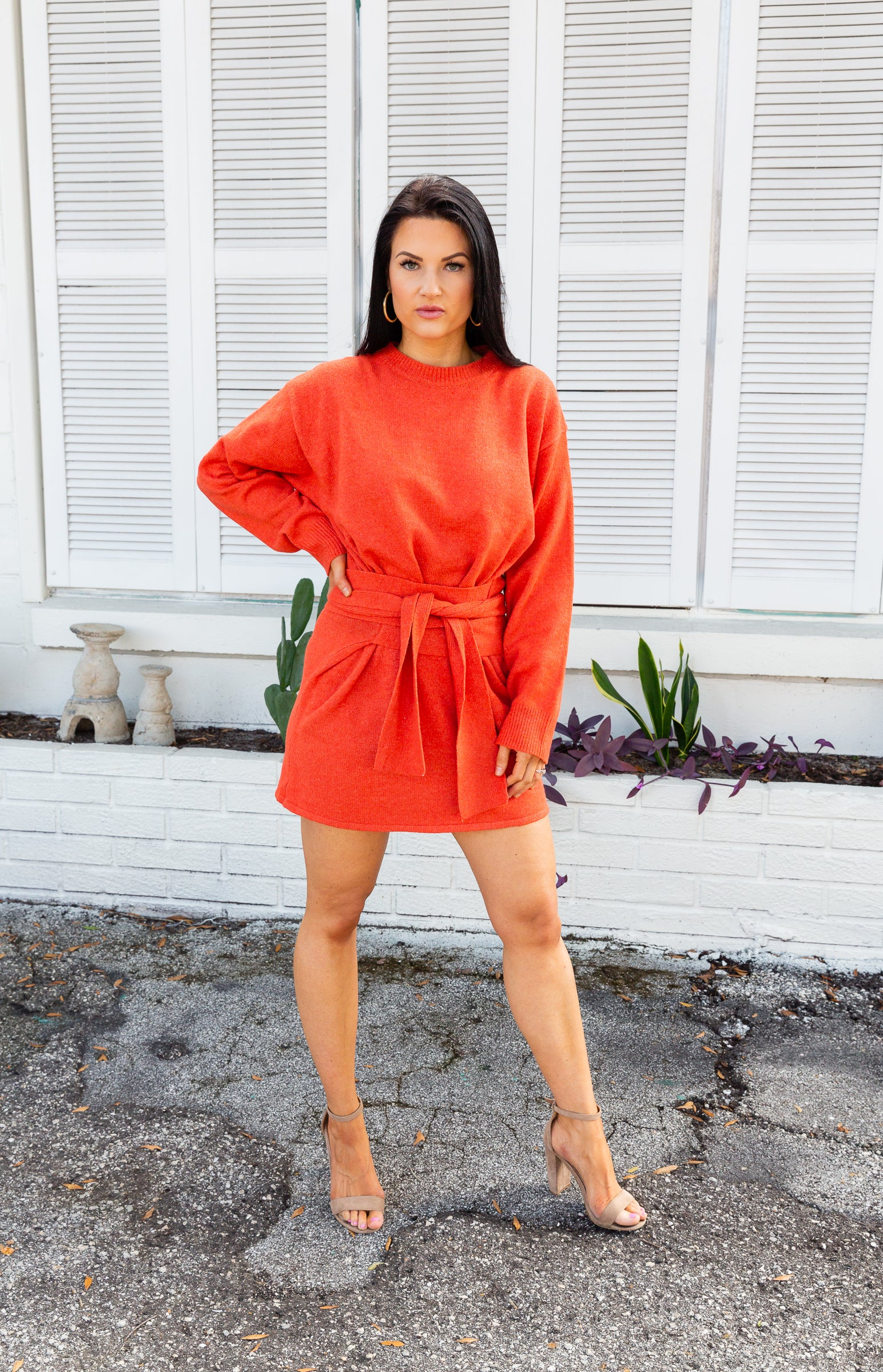 Long loose sleeves attach to a banded u-neckline on an oversized dress silhouette. It has fabric ties that come from the sides at the waist to cinch and secure at the front of the sweater dress.