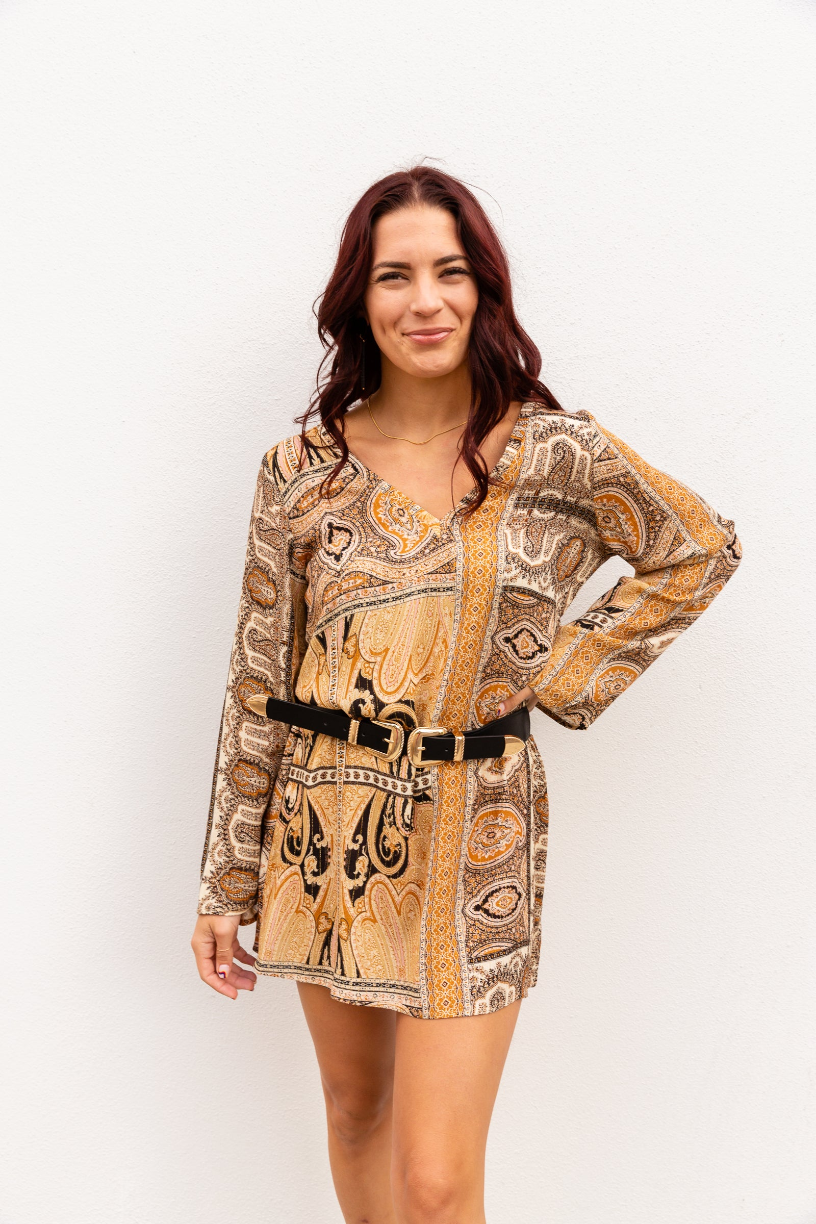 Gold threads go through the lightweight fabric of this paisley printed dress. It has long sleeves that attach to a v-neckline on a loose and comfortable shift silhouette.