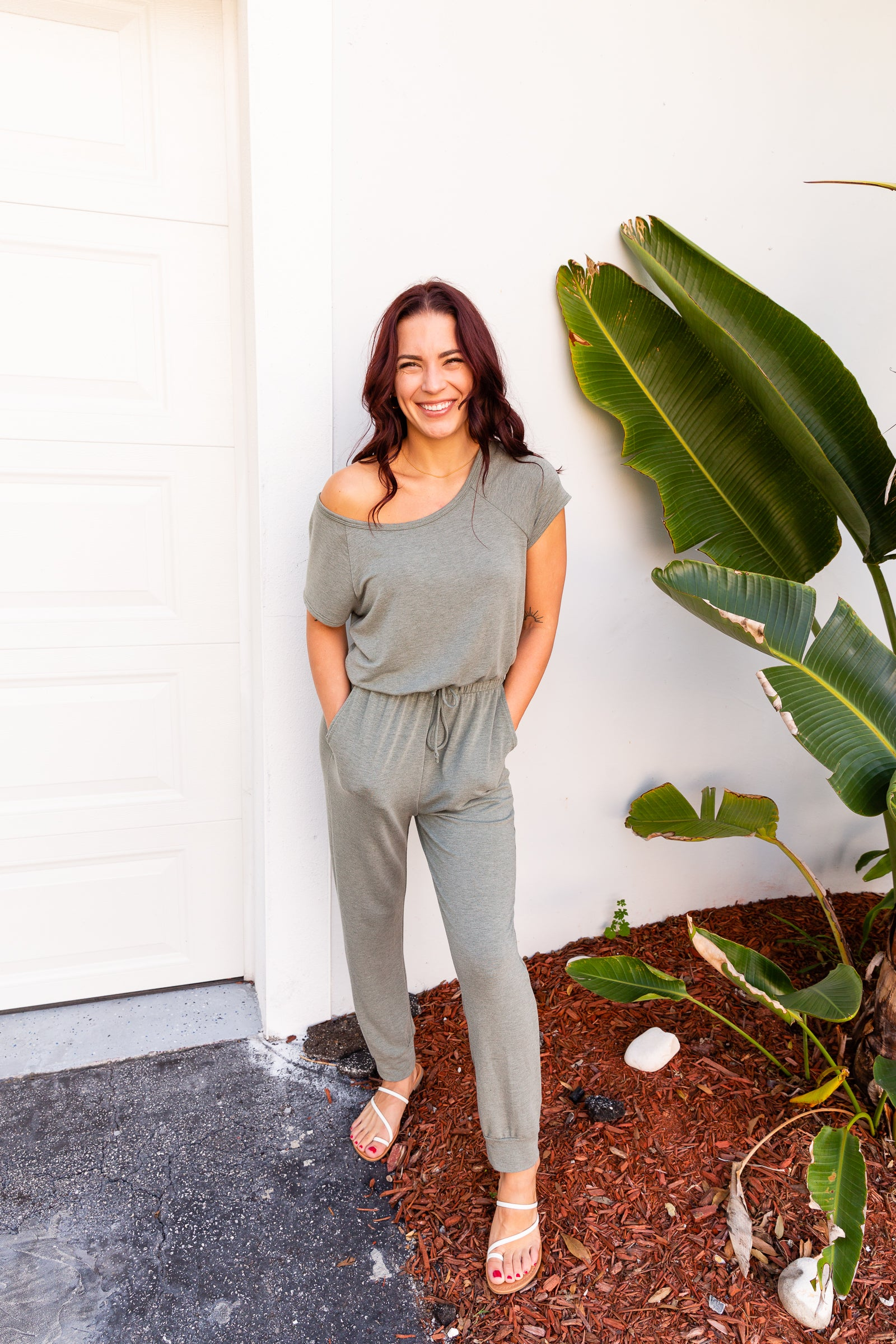 Short sleeves attach to a u-neckline on an oversized and relaxed bodice meeting an elastic waistband with a drawstring tie going down into side pockets and skinny pant legs with a banded ankle cuff.