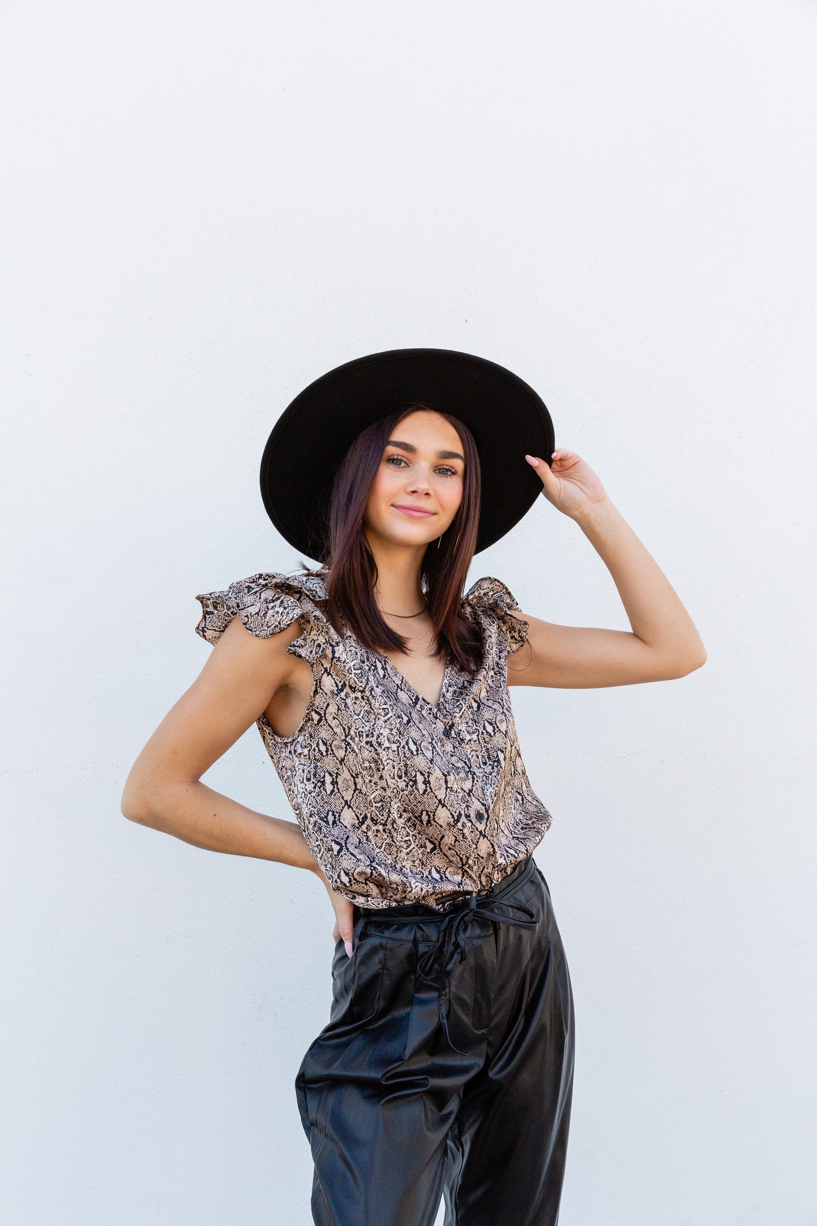 Black and tan snake prints cover the fabric of this lightweight top. It has short flutter sleeves that attach to a v-neckline on a relaxed button-down bodice silhouette.