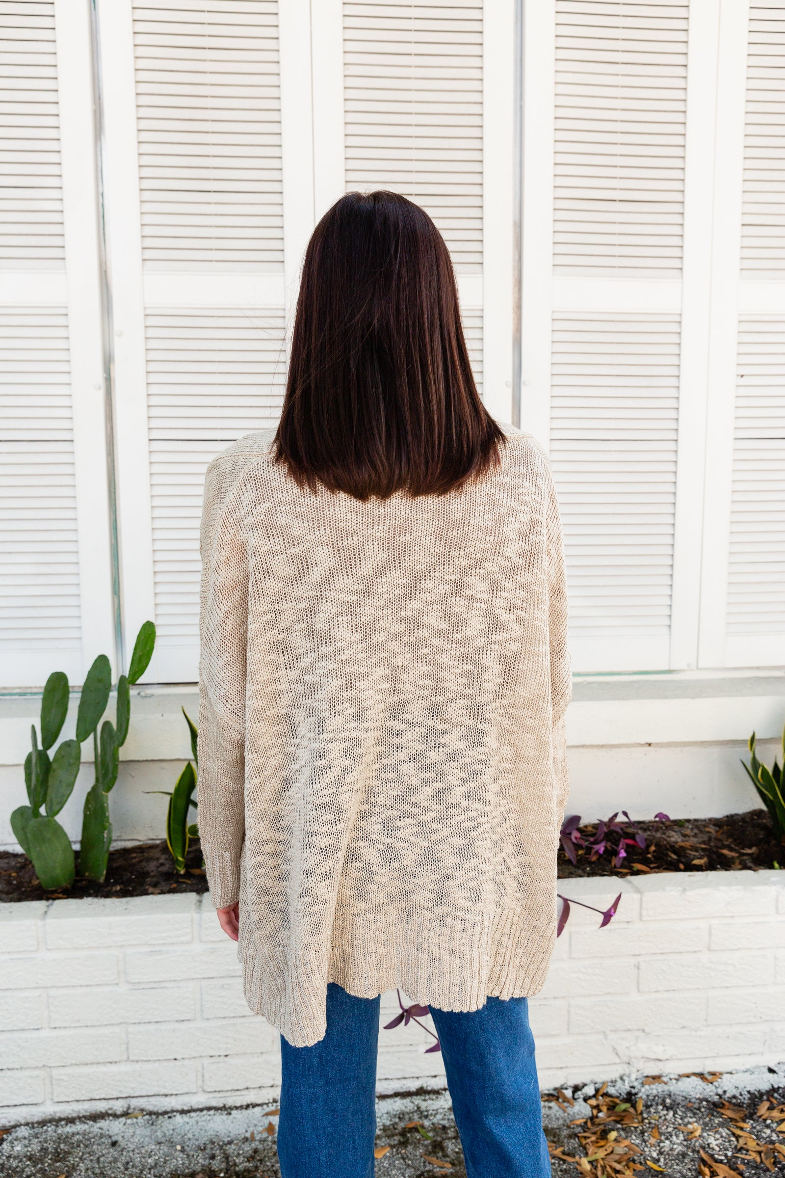 This neutral cardigan has long and loose sleeves that attach to an oversized bodice silhouette with toggle closures down the center of the overlay.