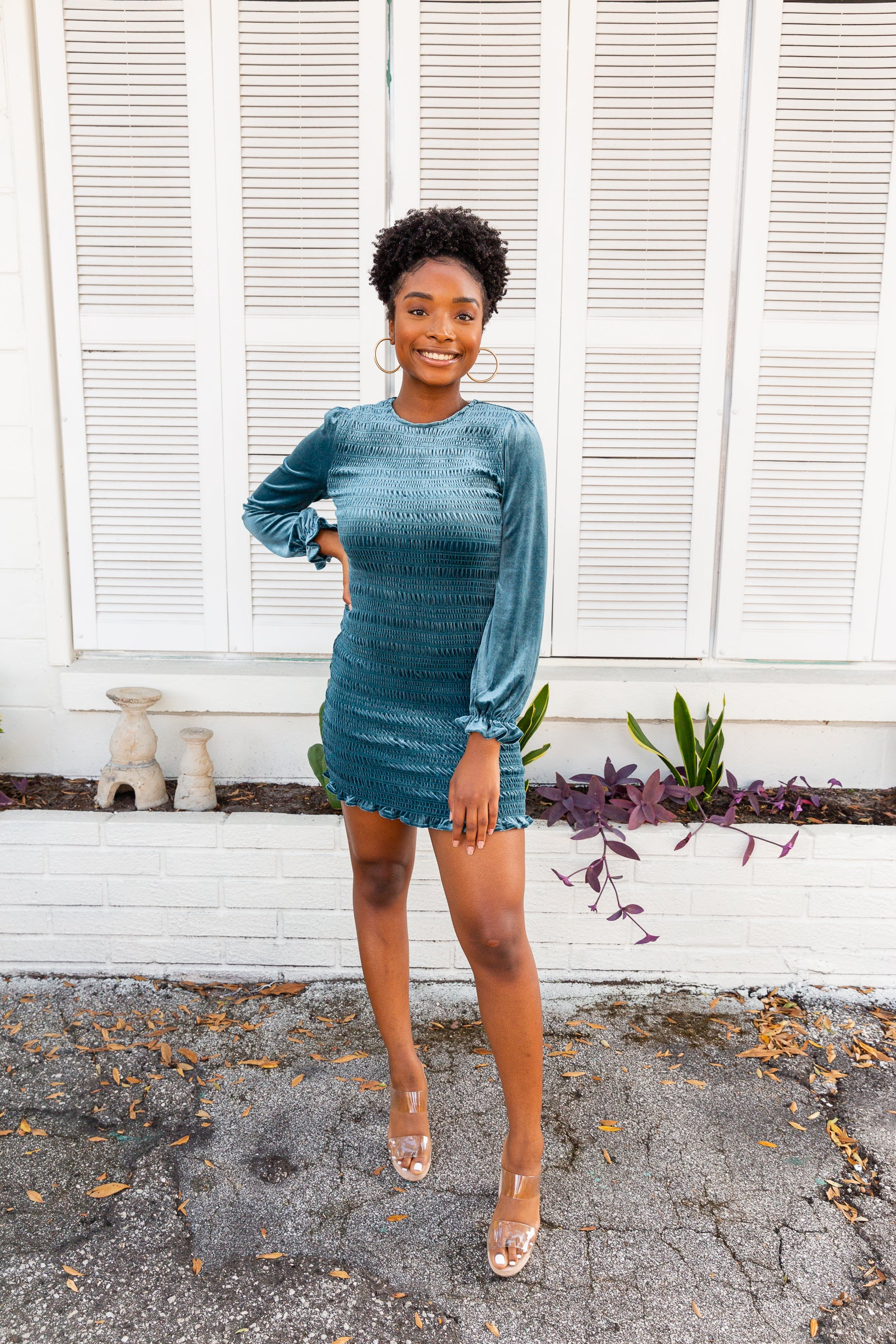 Long elastic ruffle cuffed sleeves attach to a u-neckline on a smocked bodice. This curve-hugging and bodycon dress has a ruffle trim at the bottom.