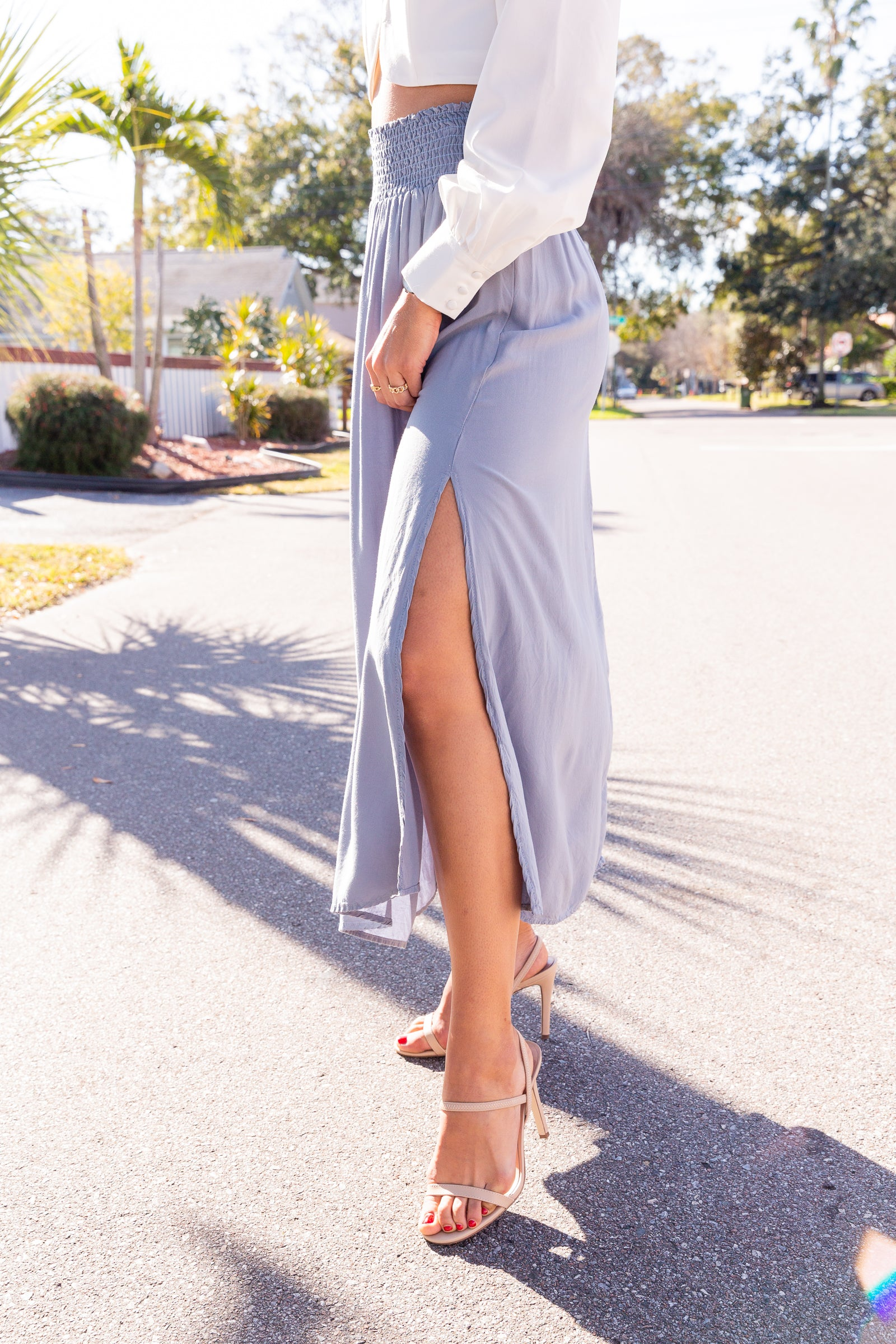 This lightweight maxi skirt has a smocked waistline that offers some stretch as it leads into a flowy skirt silhouette that hits at the ankles with a slit at the side.