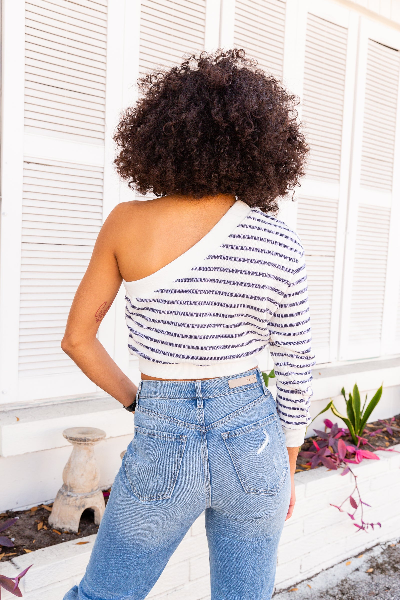 Blue stripes go across the fabric of this comfy cropped sweater. This one-shoulder top has a long banded cuffed sleeve that attaches to an asymmetrical neckline with a relaxed fit and cropped bodice.