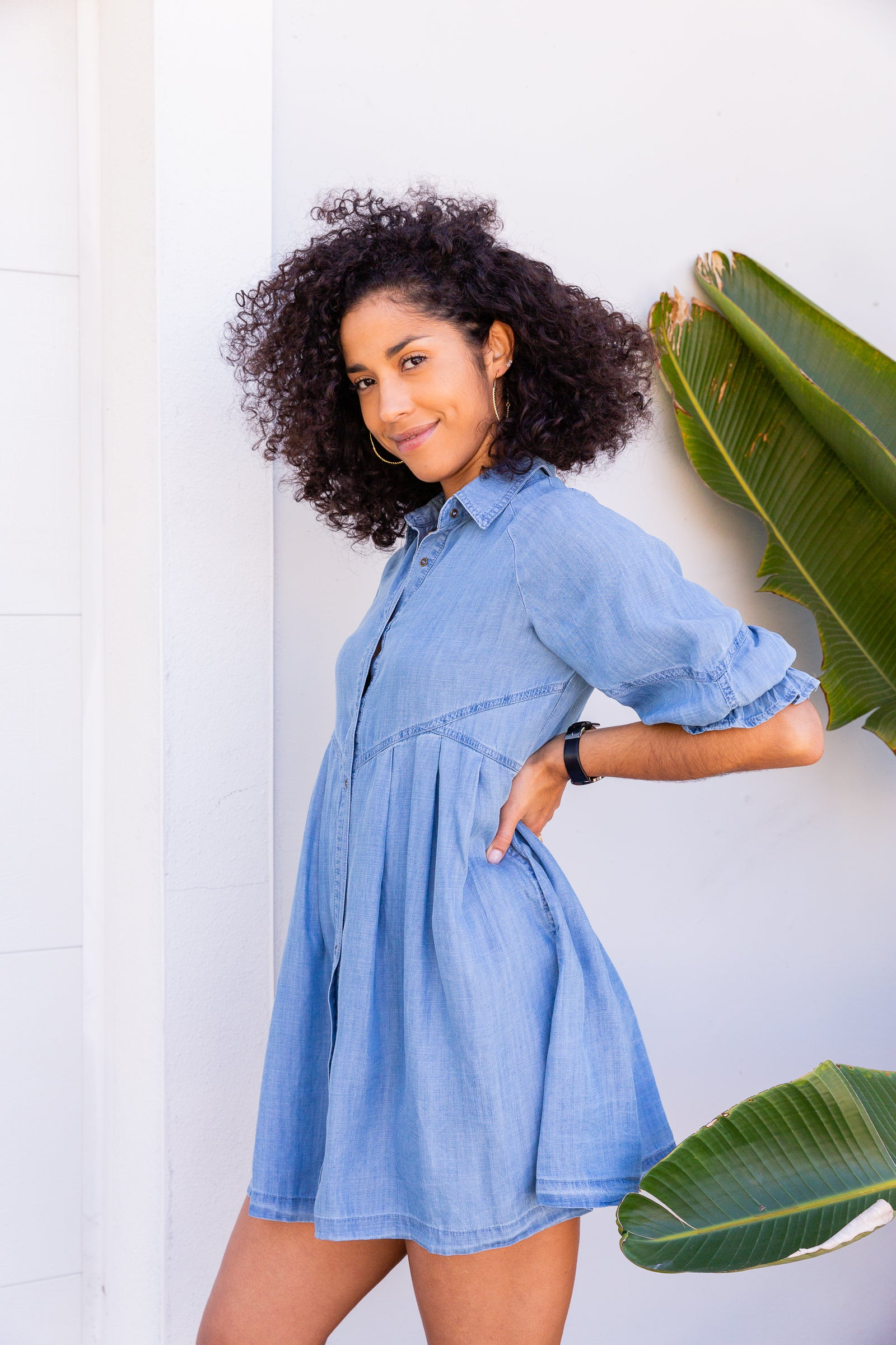 This medium wash chambray dress has mid-length elastic cuffed sleeves that attach to a collared neckline to an oversized and flowy button-down silhouette.