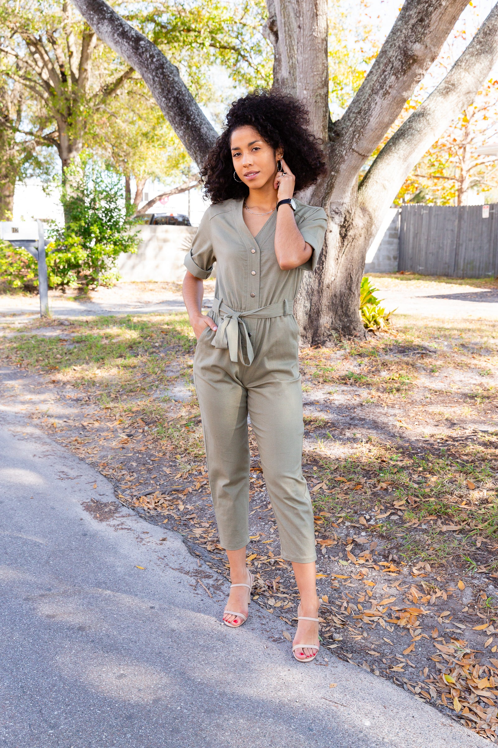 Short cuffed sleeves attach to a v-neckline on a button-down and fitted bodice before meeting an elastic waistband with belt loops. It goes into straight pant legs with side pockets.