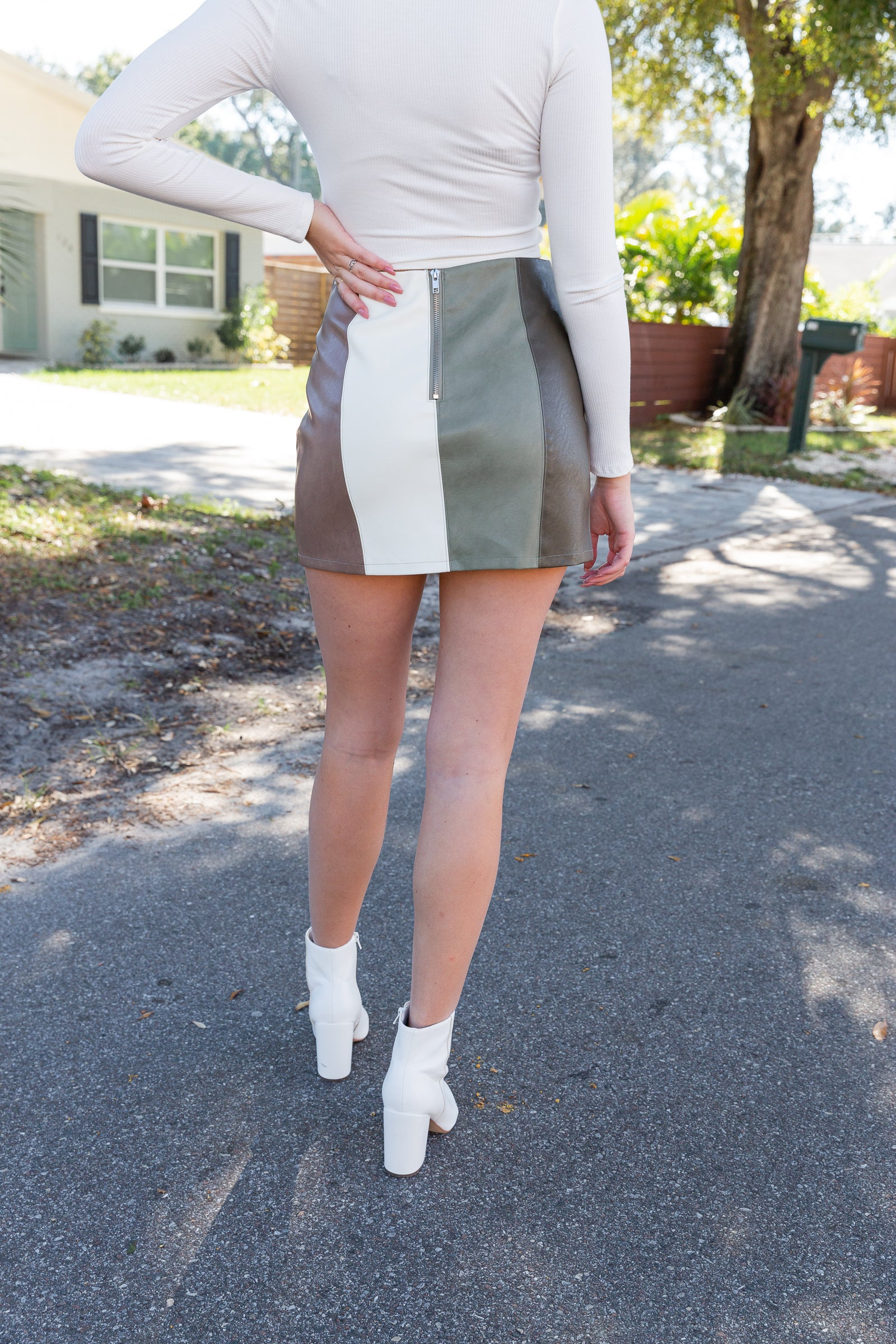 This multi-colored paneled skirt has a fitted waistband that goes into a mini pencil silhouette and has a slit at the side front of the skirt that goes up the thigh.