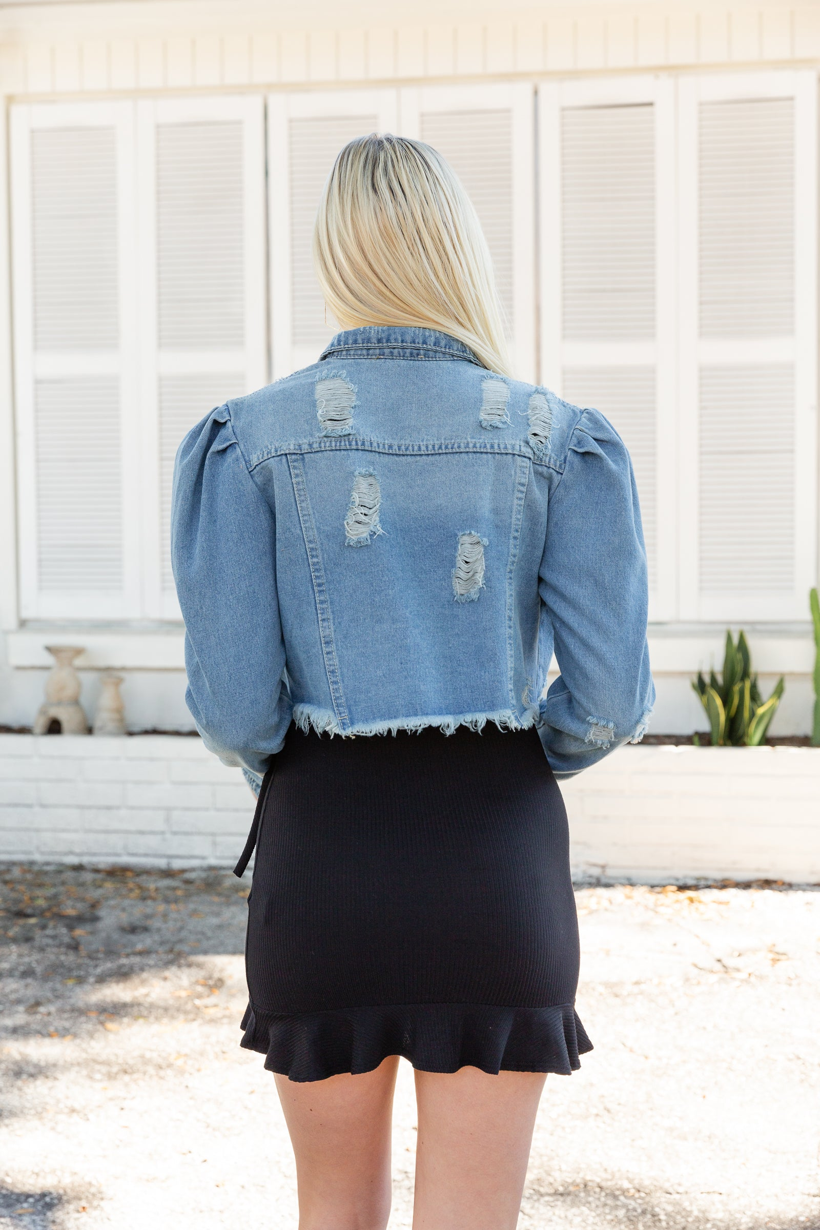 This medium wash denim jacket has long puffed shoulder sleeves that meet a collared neckline with a button-down center with two front pockets at the chest. It has a cropped bodice with a raw hem.