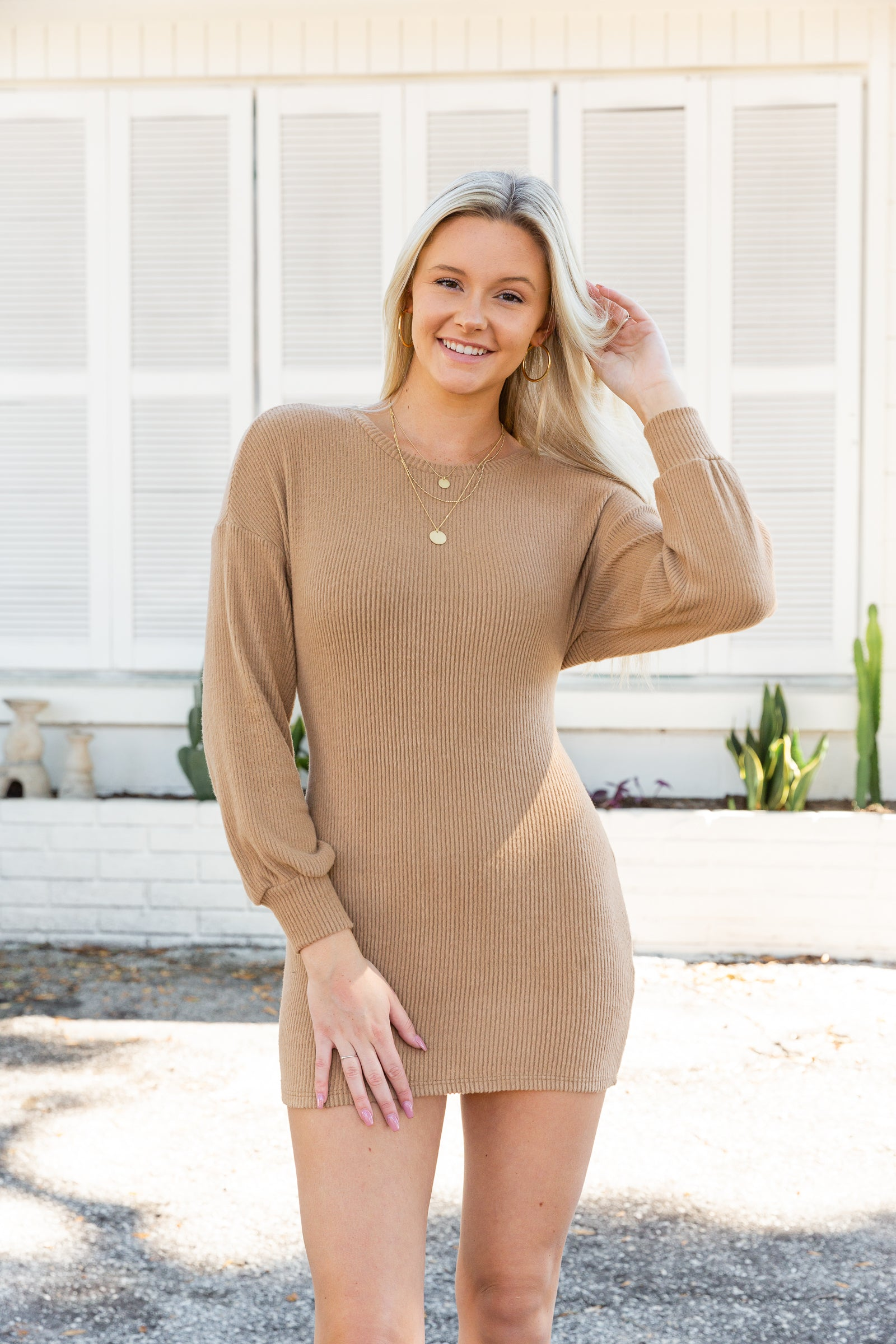 Long banded cuff sleeves attach to a high crew neckline on a curve-accentuating bodice and mini skirt silhouette. This sweater dress has an exposed open back that is secured with a tie hem.