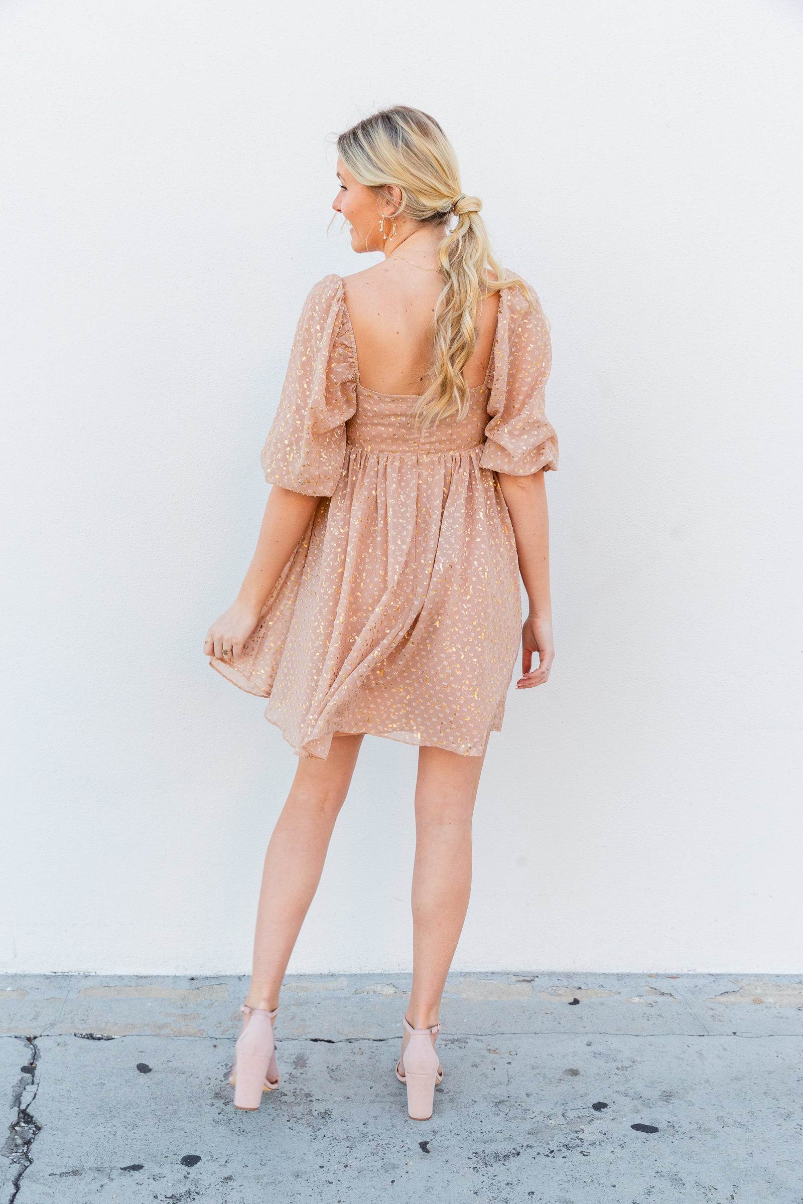 Gold prints cover the flowy fabric of this dress. Mid-length puff sleeves attach to a square neckline on a darted top that flows into an oversized babydoll shift dress silhouette.