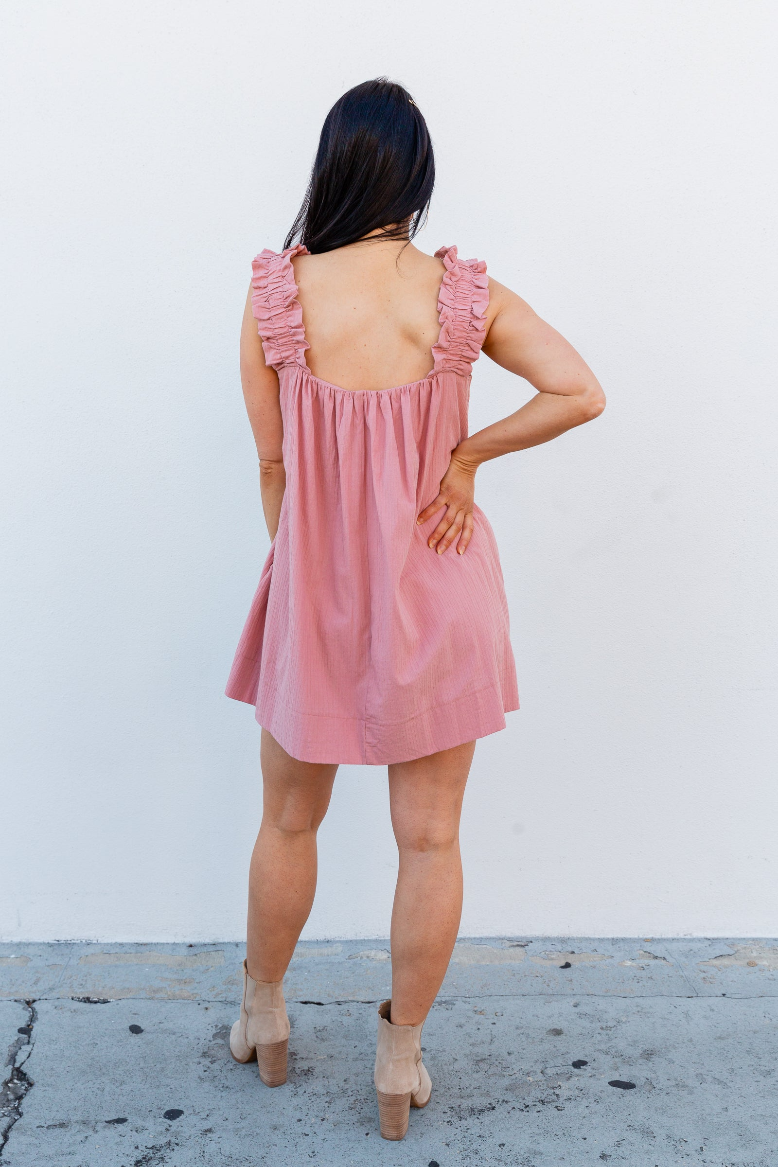 This darling faux-dress style romper has medium ruffle straps that attach to a straight neckline on a relaxed bodice before going into a babydoll skirt with pockets at the side.