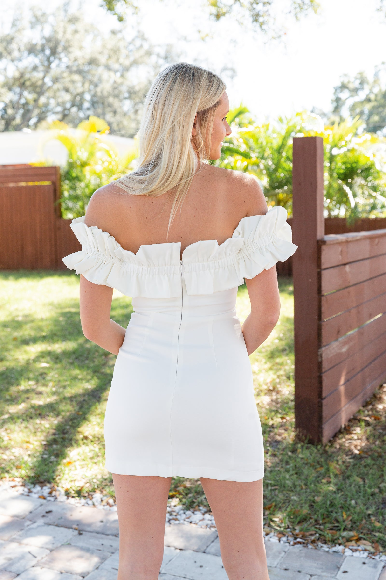 This chic white dress has short off-the-shoulder sleeves that attach onto a straight neckline on a fitted and darted bodice leading to a fitted waistband and leading into a short a-line mini skirt.