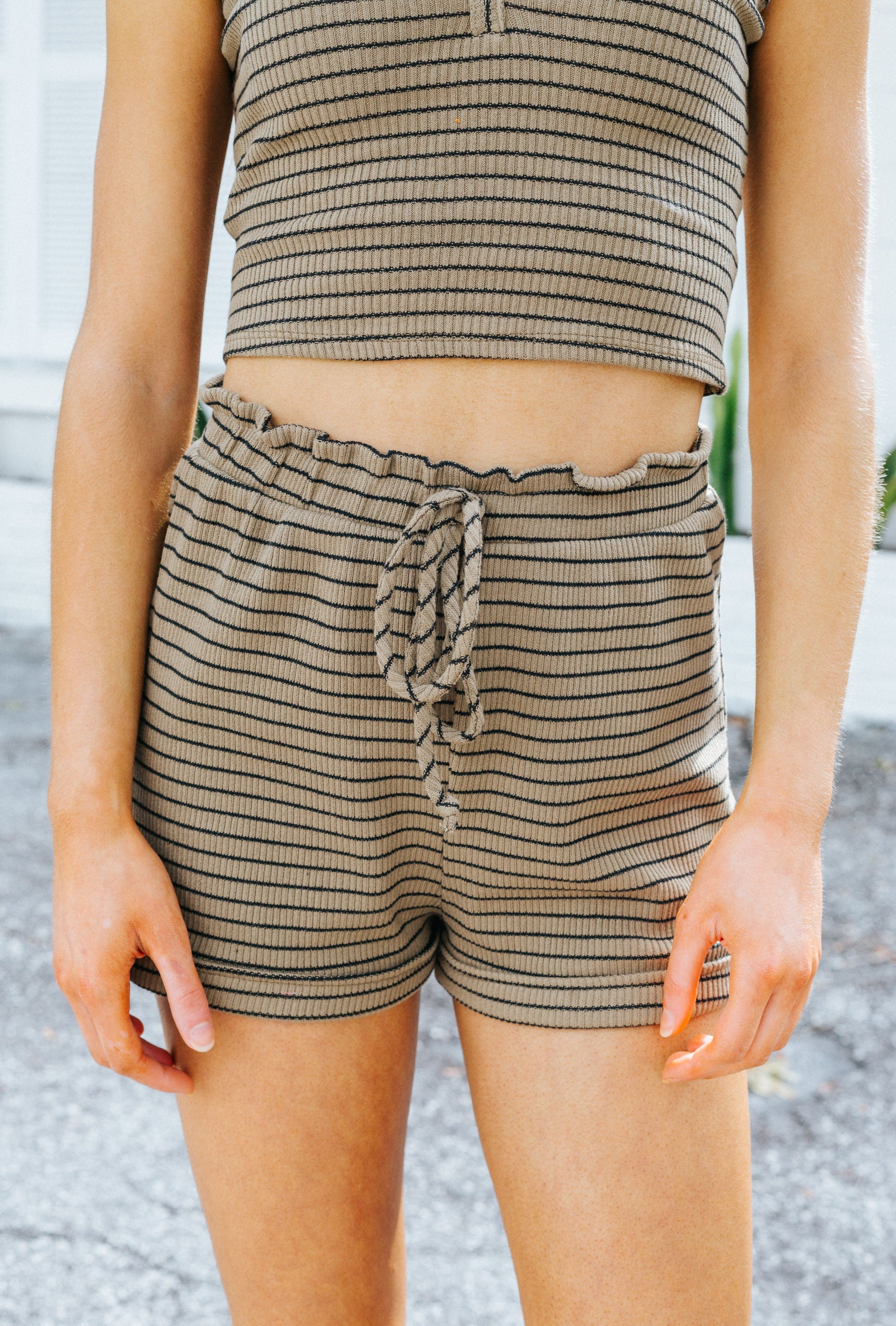 Black stripes that go across the ribbed fabric. It has an elastic waistband with a faux drawstring tie and goes down into loose shorts with thick banded bottom hem.