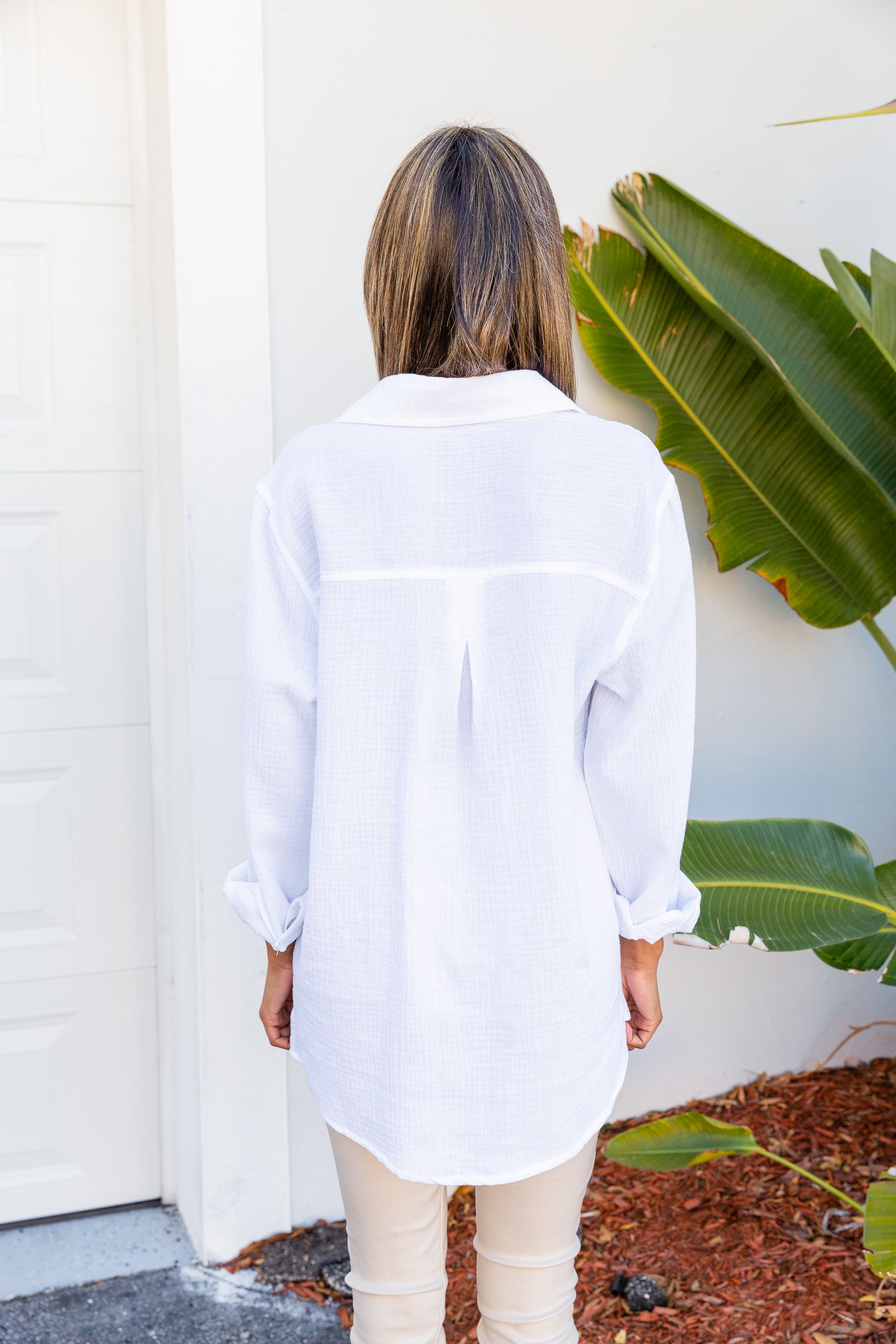 This collared top has long cuffed sleeves that attach to a banded button-down and oversized bodice with front pockets at the chest.