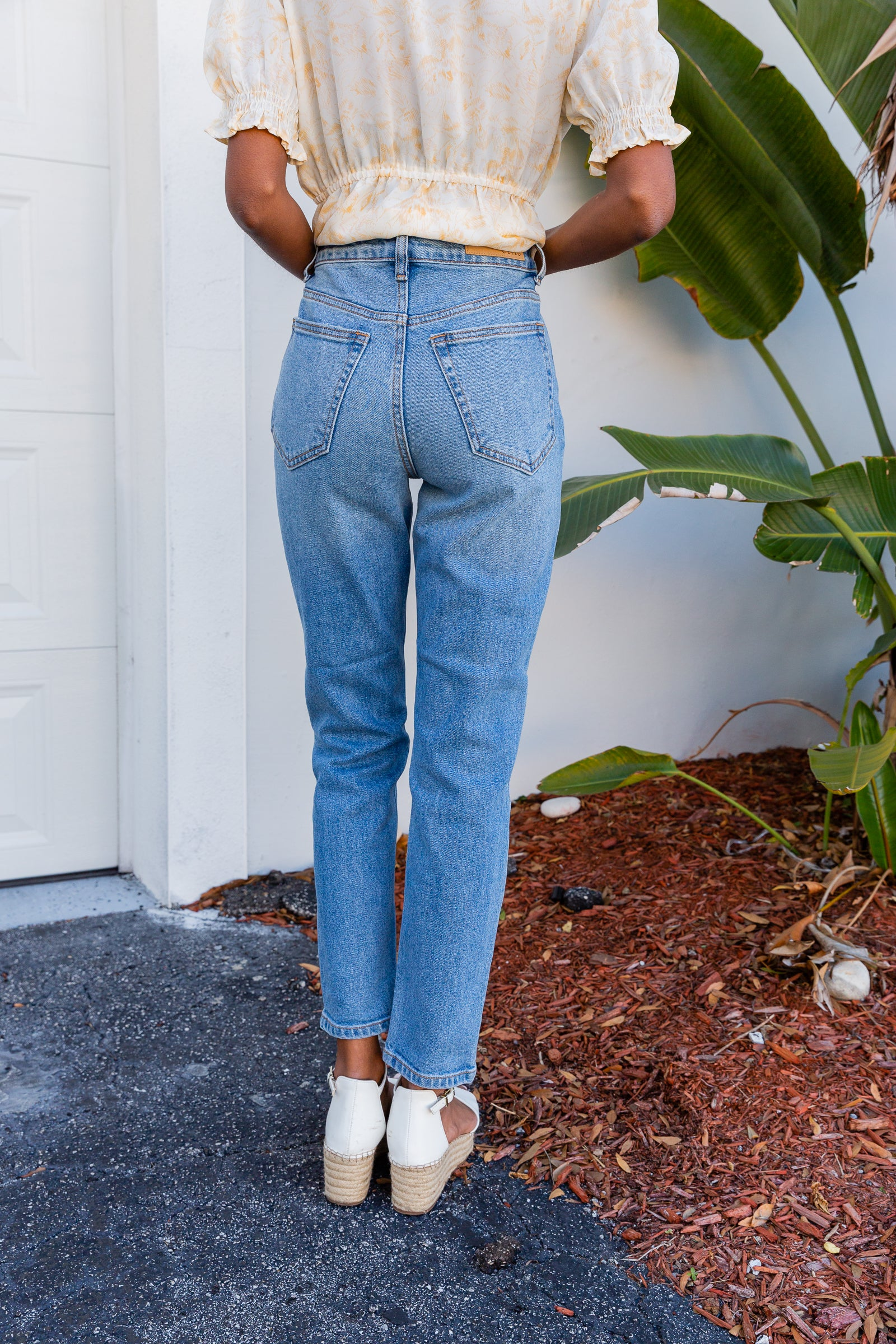 These medium-wash denim jeans have a fitted waistband with belt loops leading to a zipper fly and have a traditional 5-pocket structure and go down into straight pant legs ending in a clean hem.