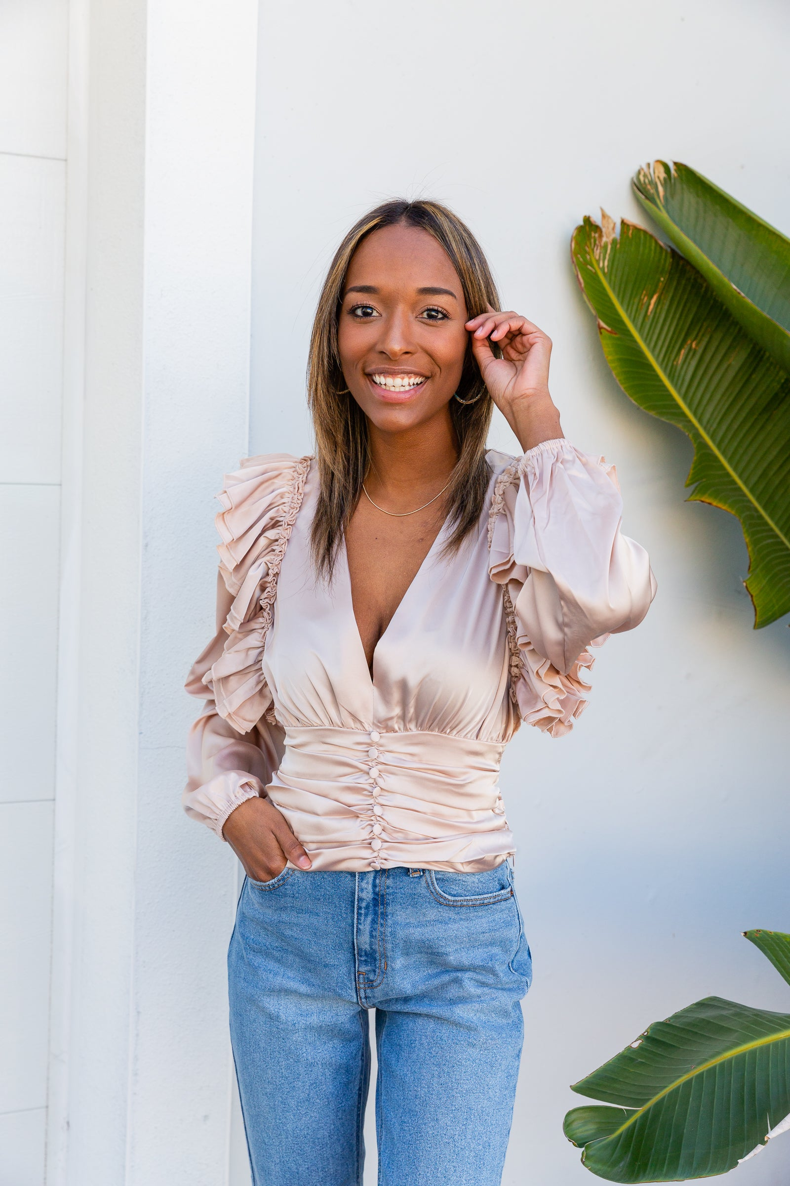 Long elastic cuffed sleeves meet a ruffle hem that goes down the shoulders of a deep v-neckline bodice. At the waistband, the top meets a button-down detail atop gathered fabric.