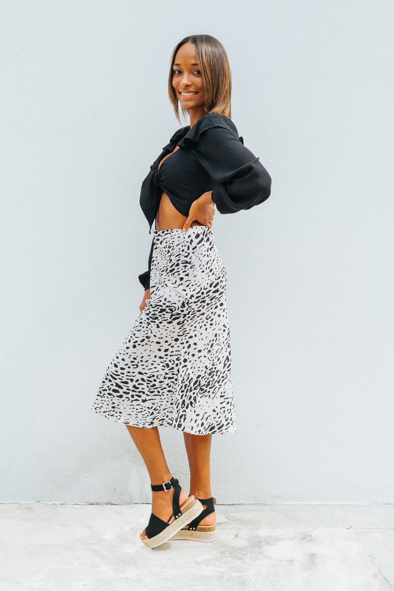 Leopard prints cover the fabric of this stunning midi skirt. It has an elastic waistband that hits at the small of the waist and flows down into a bias cut and flirty midi skirt.