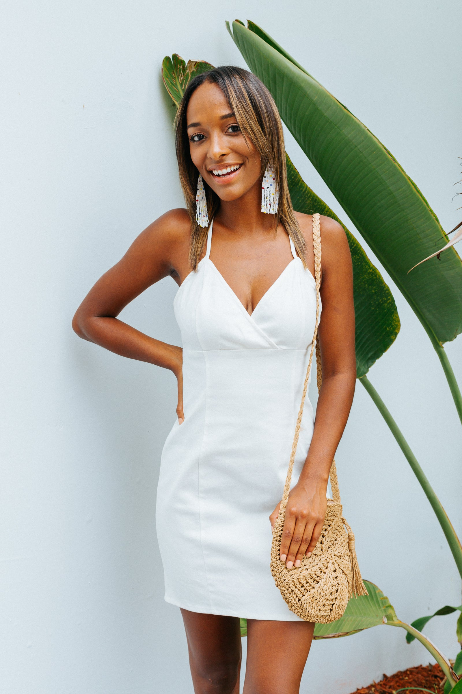 This chic white mini dress has thin straps that attach to a surplice neckline on a darted bodice and meets a body and hip-hugging dress silhouette.