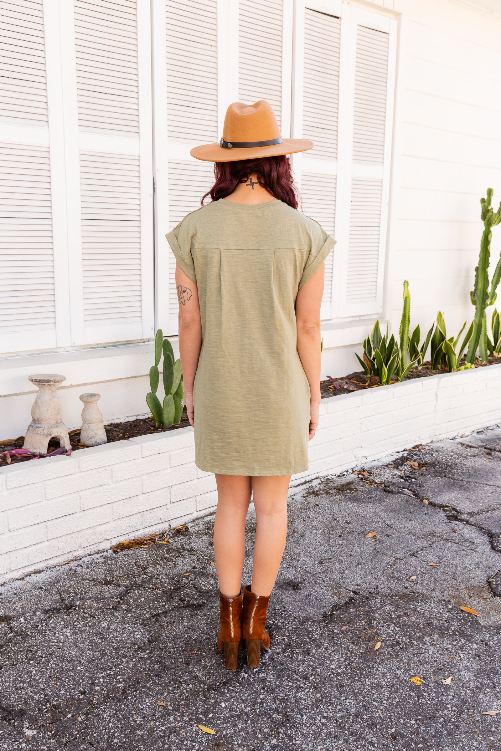 Short rolled sleeves attach to a crew neckline on a loose and relaxed fit dress with side pockets. This tee dress features a front pocket to detail the chest.