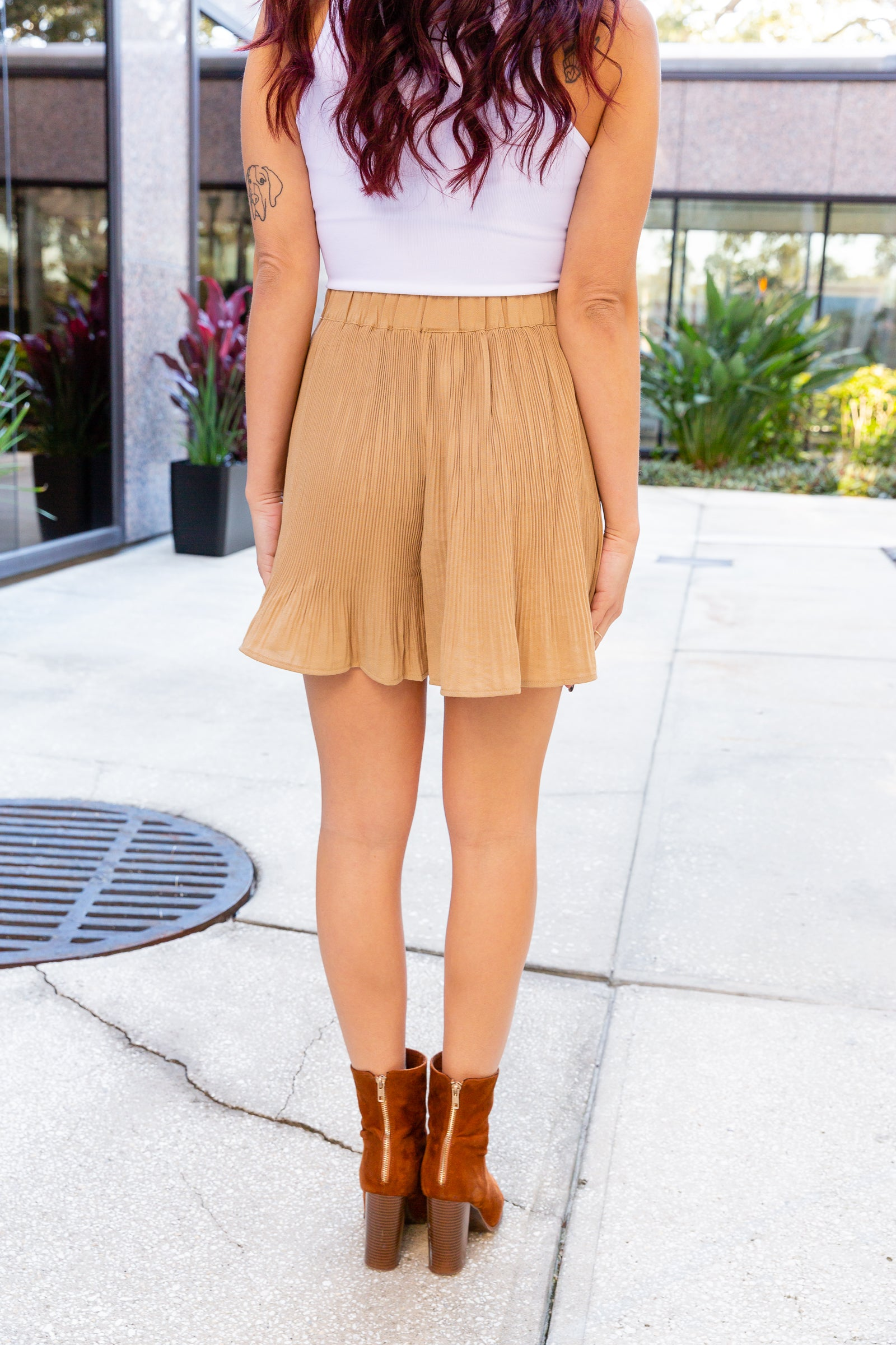 These adorable shorts have an elastic waistband that goes into pleated comfortable shorts with ruffle trim at the bottom. These pleated shorts feature a fabric tie to cinch at the waist.