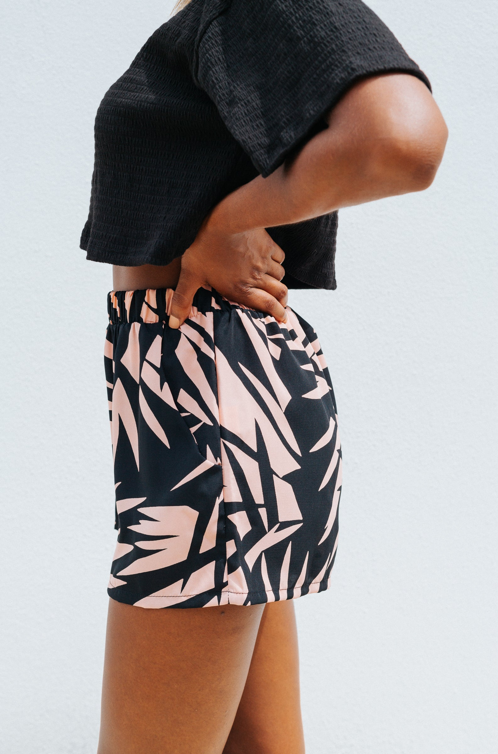 Pink peachy tropical prints cover the fabric of these fun summer shorts. It has an elastic waistband and goes down into side pockets on relaxed shorts.